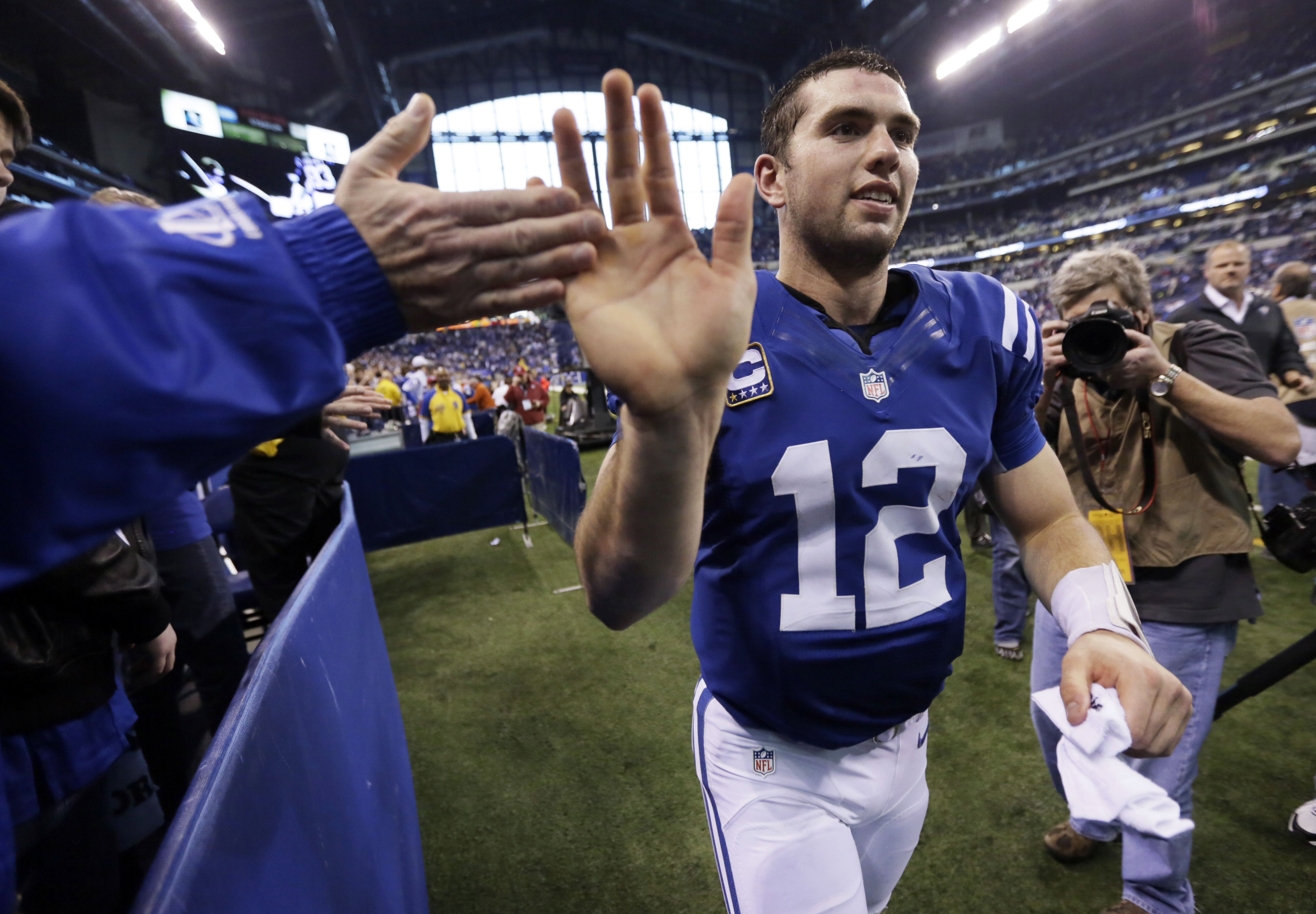 FILE - In this Dec. 30, 2012, file photo, Indianapolis Colts' Andrew Luck (12) is congratulated by a fan as he leaves the field after the Colts defeated the Houston Texans, 28-16, in an NFL football game in Indianapolis. Luck and Washington Redskins quart