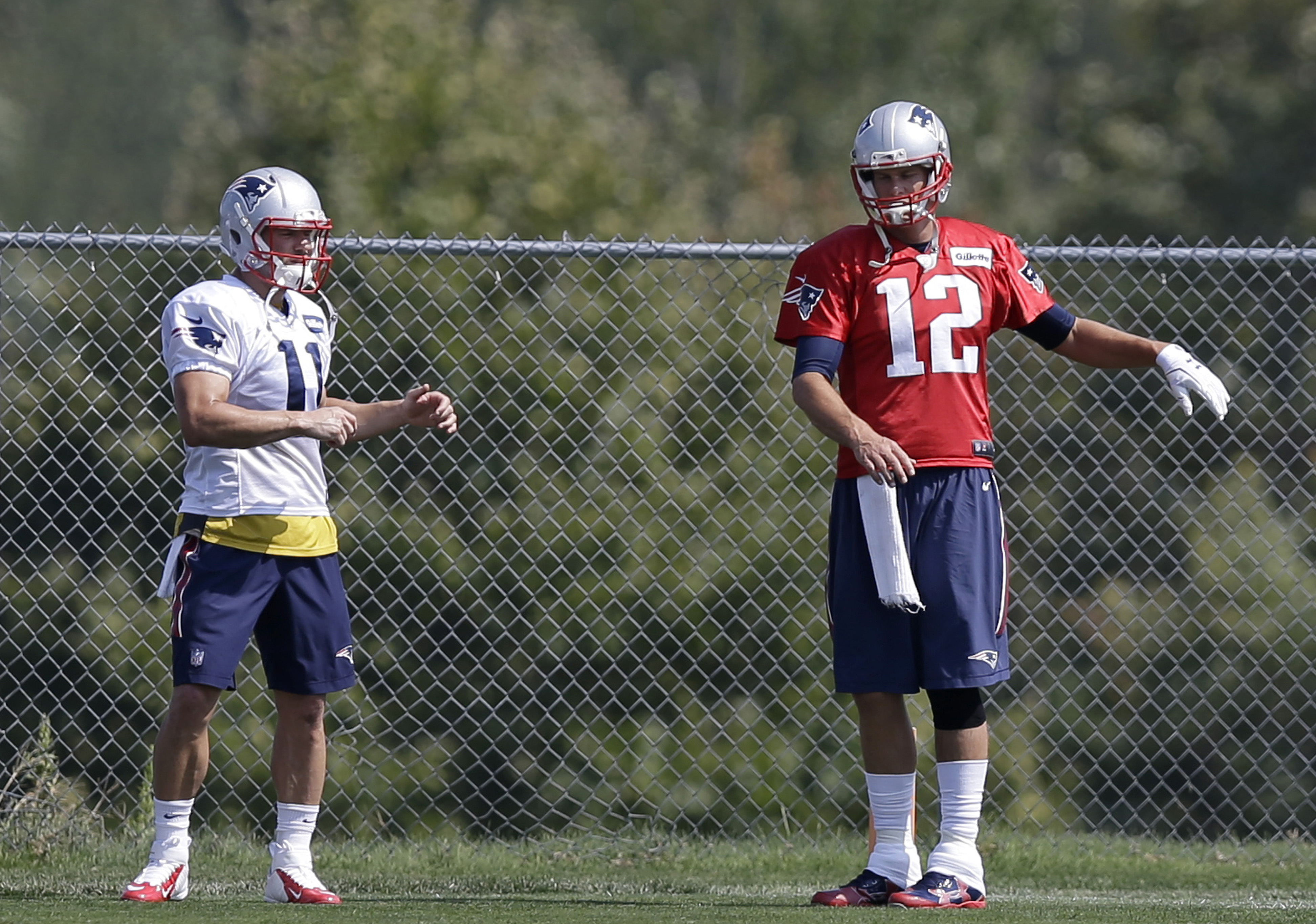 New England Patriots wide receiver Julian Edelman, left, and quarterback Tom Brady, right, stretch as they warm up on the field during an NFL football practice, Tuesday, Sept. 8, 2015, in Foxborough, Mass. (AP Photo/Steven Senne)