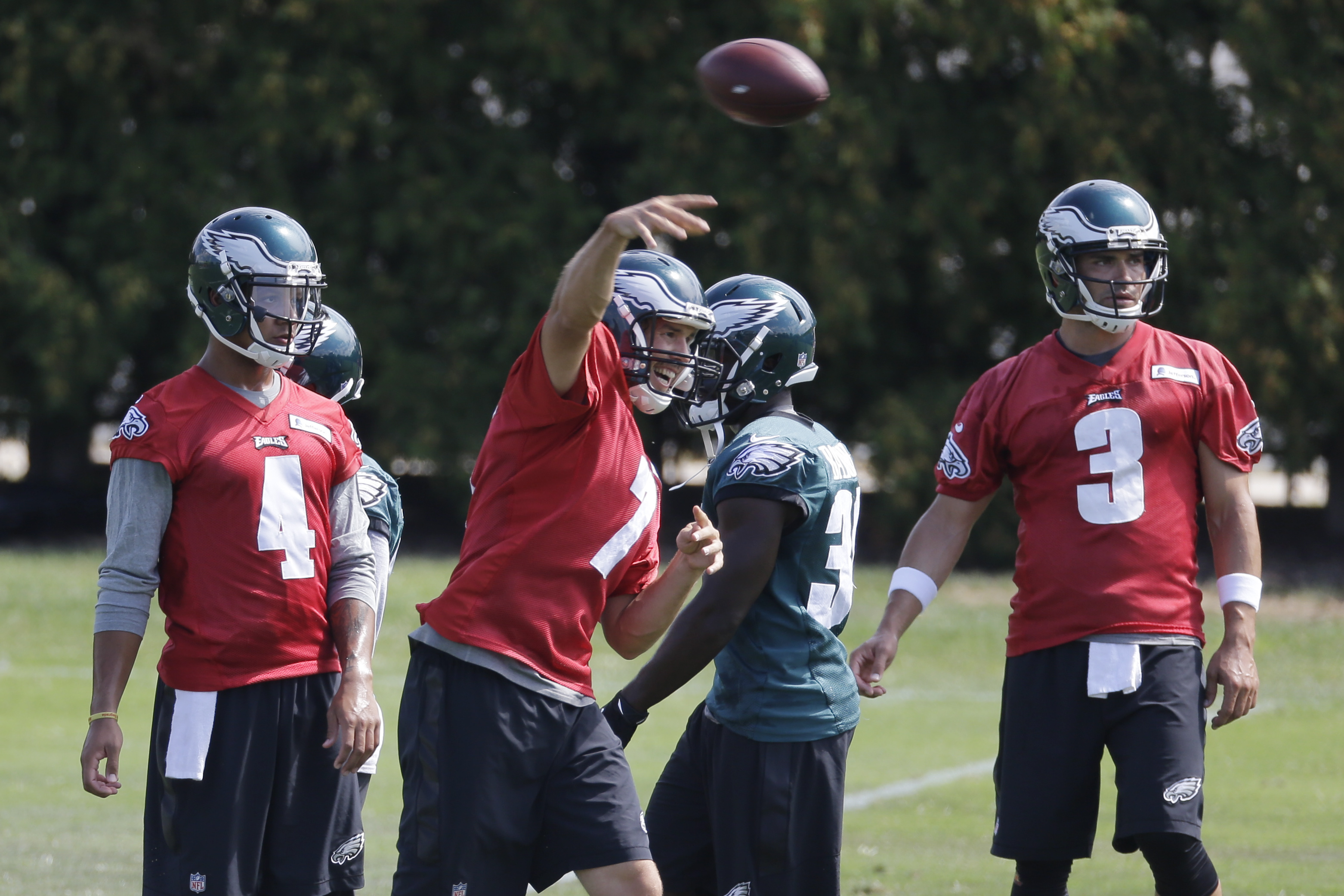 Philadelphia Eagles quarterback Sam Bradford (7) throws a pass as quarterbacks Stephen Morris (4) and Mark Sanchez look on at the NFL football team's practice facility, Wednesday, Sept. 9, 2015, in Philadelphia. (AP Photo/Matt Rourke)