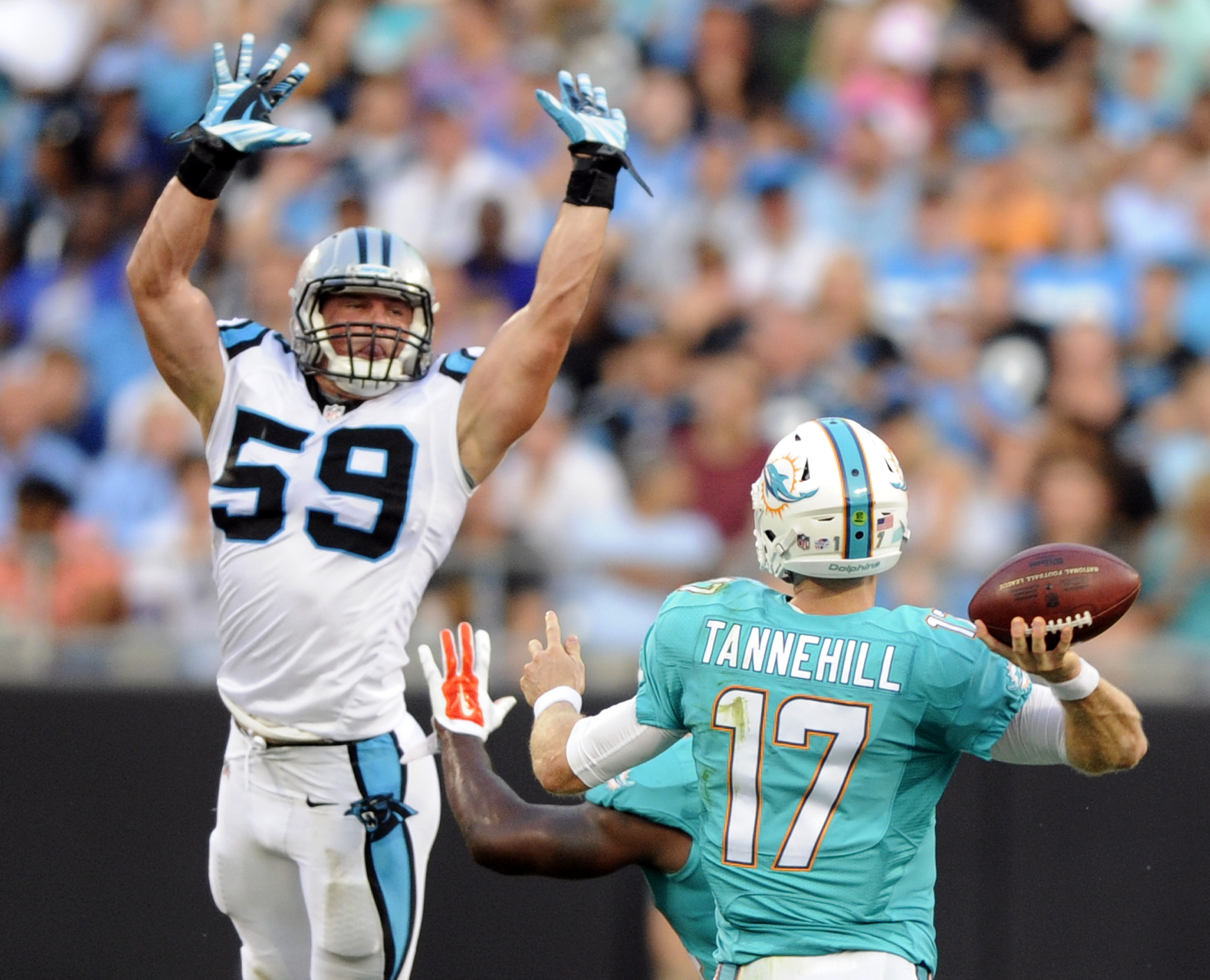 In this photo taken Aug. 22, 2015 Miami Dolphins' Ryan Tannehill (17) looks to pass over Carolina Panthers' Luke Kuechly (59) during the first half of an NFL preseason football game in Charlotte, N.C. A person familiar with the situation says Luke Kuechly