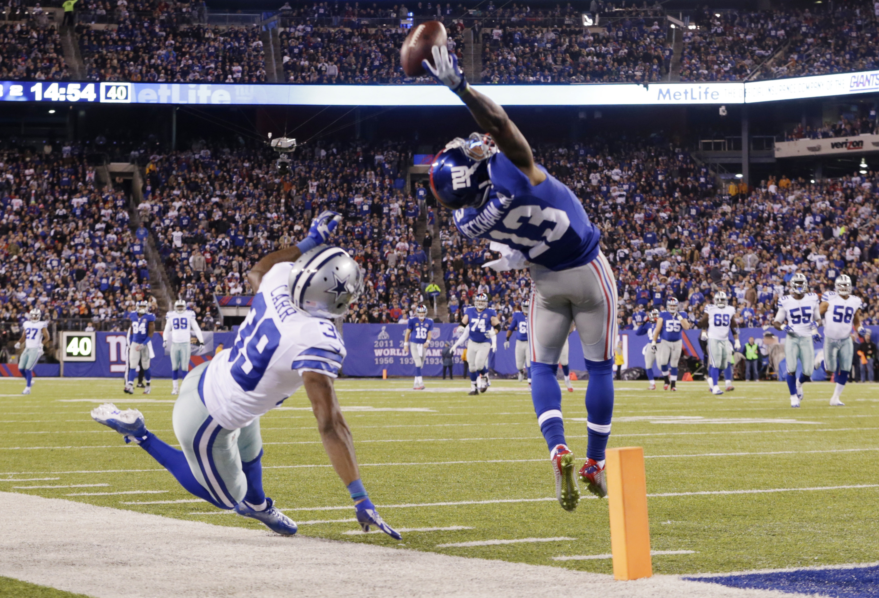 FILE - In this Nov. 23, 2014, file photo, New York Giants wide receiver Odell Beckham Jr. (13) makes a one-handed catch for a touchdown against Dallas Cowboys cornerback Brandon Carr (39) in the second quarter of an NFL football game in East Rutherford, N