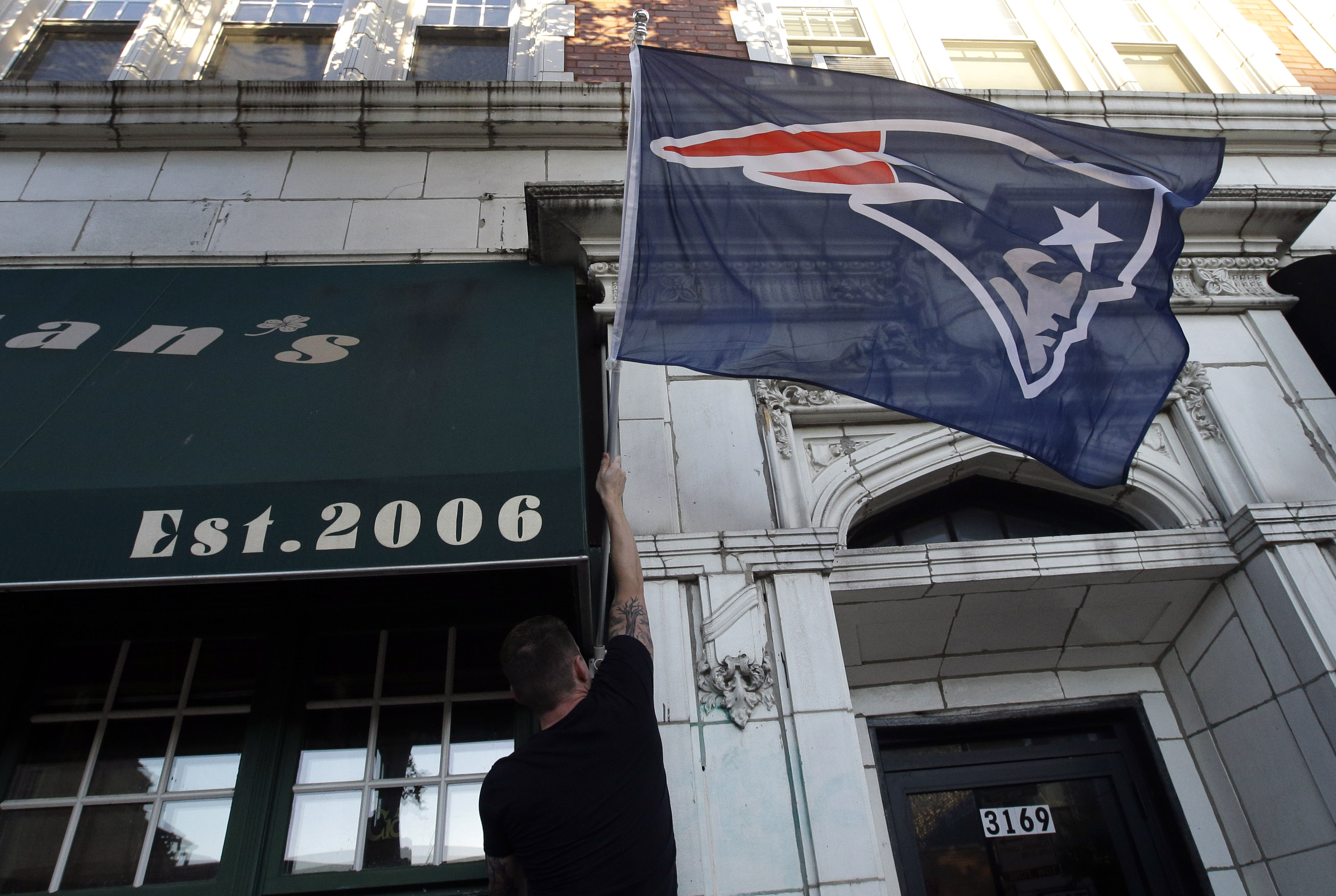 Michael Simoneau, of Chicago, hangs a New England Patriots' flag at Brendan's Pub before an NFL football game between the Pittsburgh Steelers and the Patriots on Thursday, Sept. 10, 2015, in Chicago. Friends who are Patriots fans are coming to town, and y