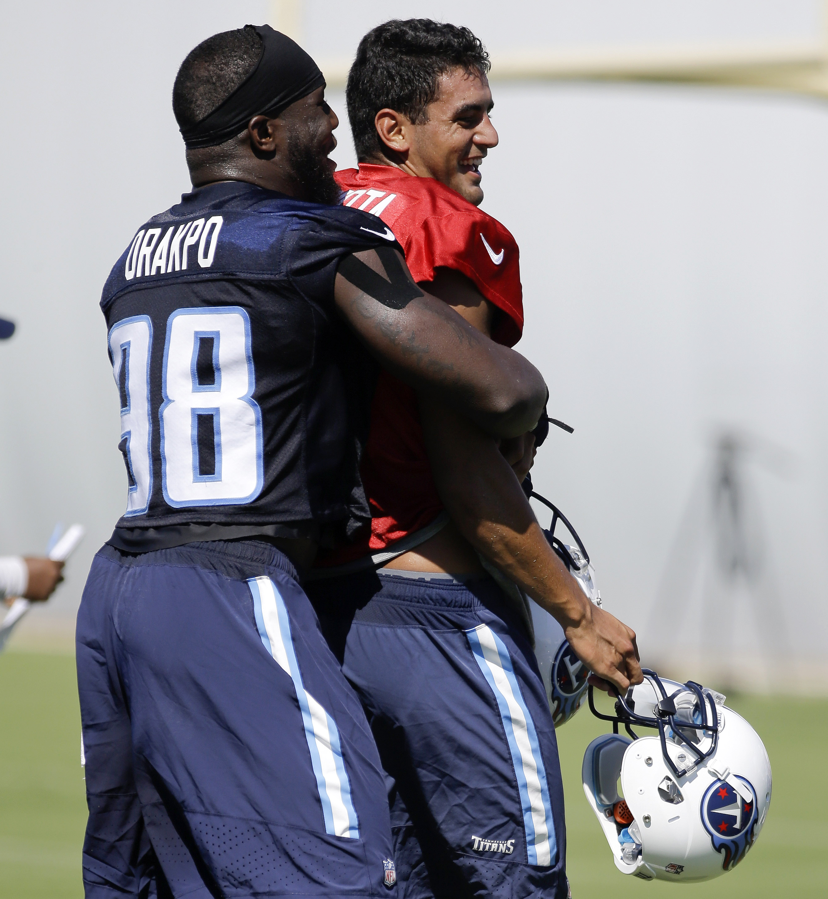 FILE - In this July 31, 2015, file photo, Tennessee Titans linebacker Brian Orakpo (98) hugs quarterback Marcus Mariota, right, during the first day of NFL football training camp in Nashville, Tenn. Titans linebacker Brian Orakpo is a teammate of Heisman