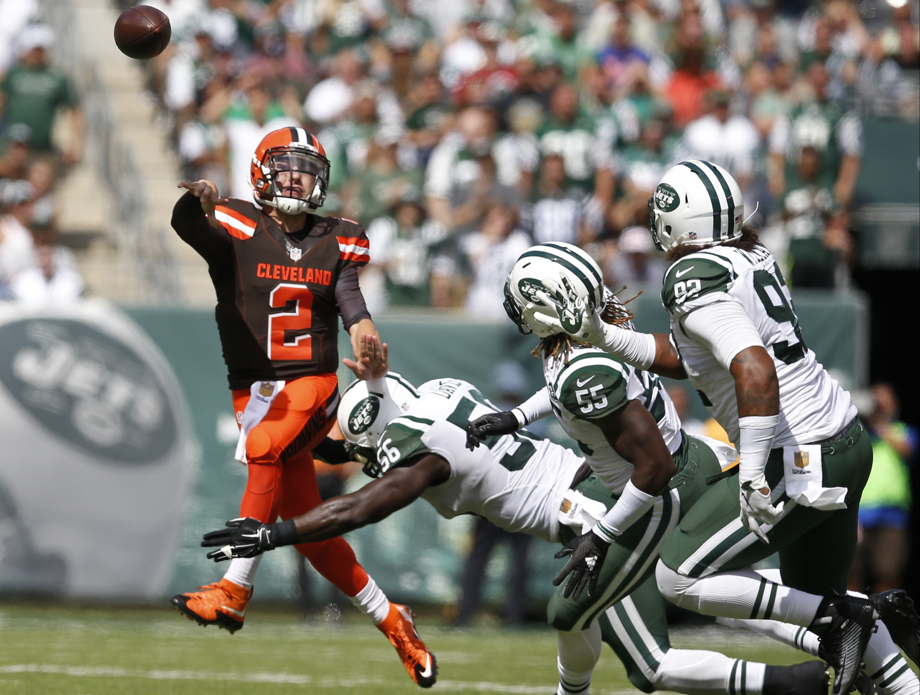 Cleveland Browns quarterback Johnny Manziel (2) throws a pass while evading New York Jets inside linebacker Demario Davis (56), Lorenzo Mauldin (55) and Kevin Vickerson (92) during the first half of an NFL football game Sunday, Sept. 13, 2015 in East Ruth