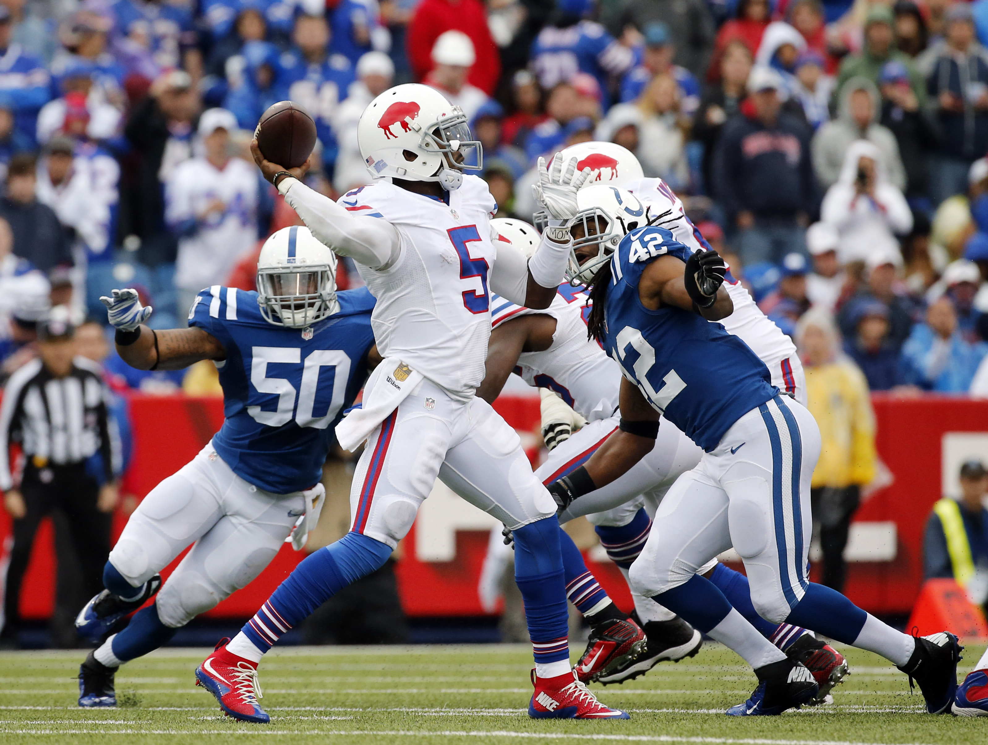 Buffalo Bills quarterback Tyrod Taylor (5) passes while under pressure from Indianapolis Colts inside linebacker Jerrell Freeman (50) and strong safety Clayton Geathers (42) during the second half of an NFL football game on Sunday, Sept. 13, 2015, in Orch