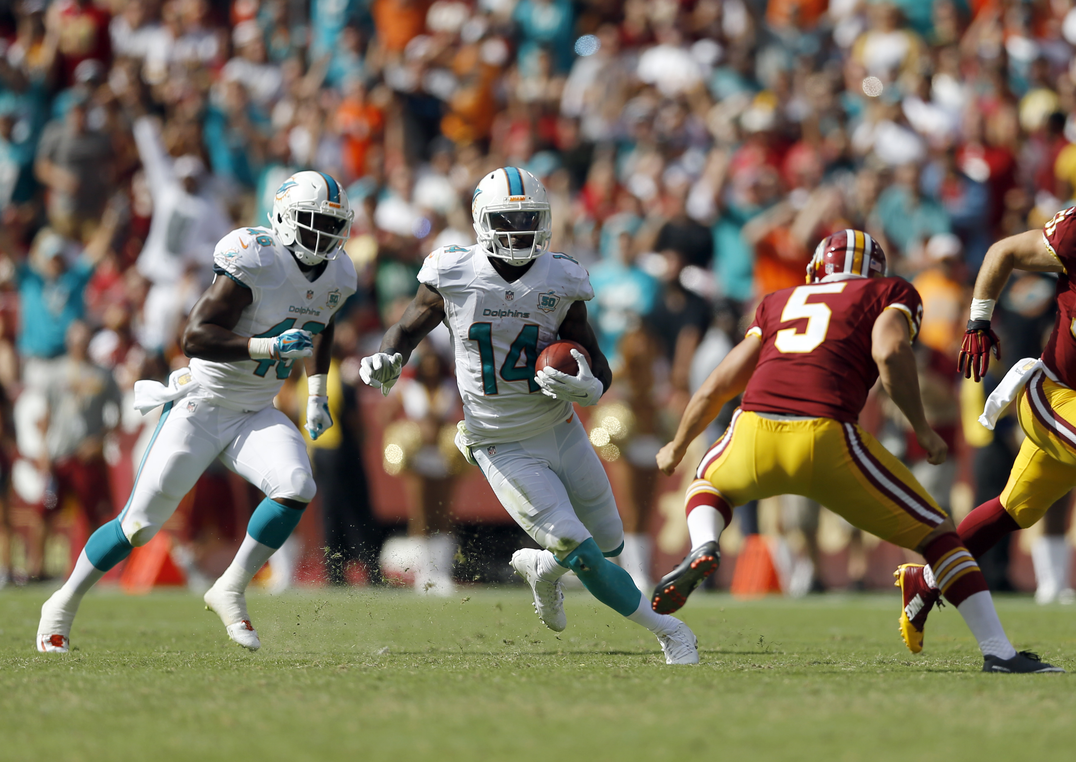 Miami Dolphins wide receiver Jarvis Landry (14) returns a punt 69 yards for a touchdown past Washington Redskins punter Tress Way (5) during the second half of an NFL football game Sunday, Sept. 13, 2015, in Landover, Md. (AP Photo/Patrick Semansky)