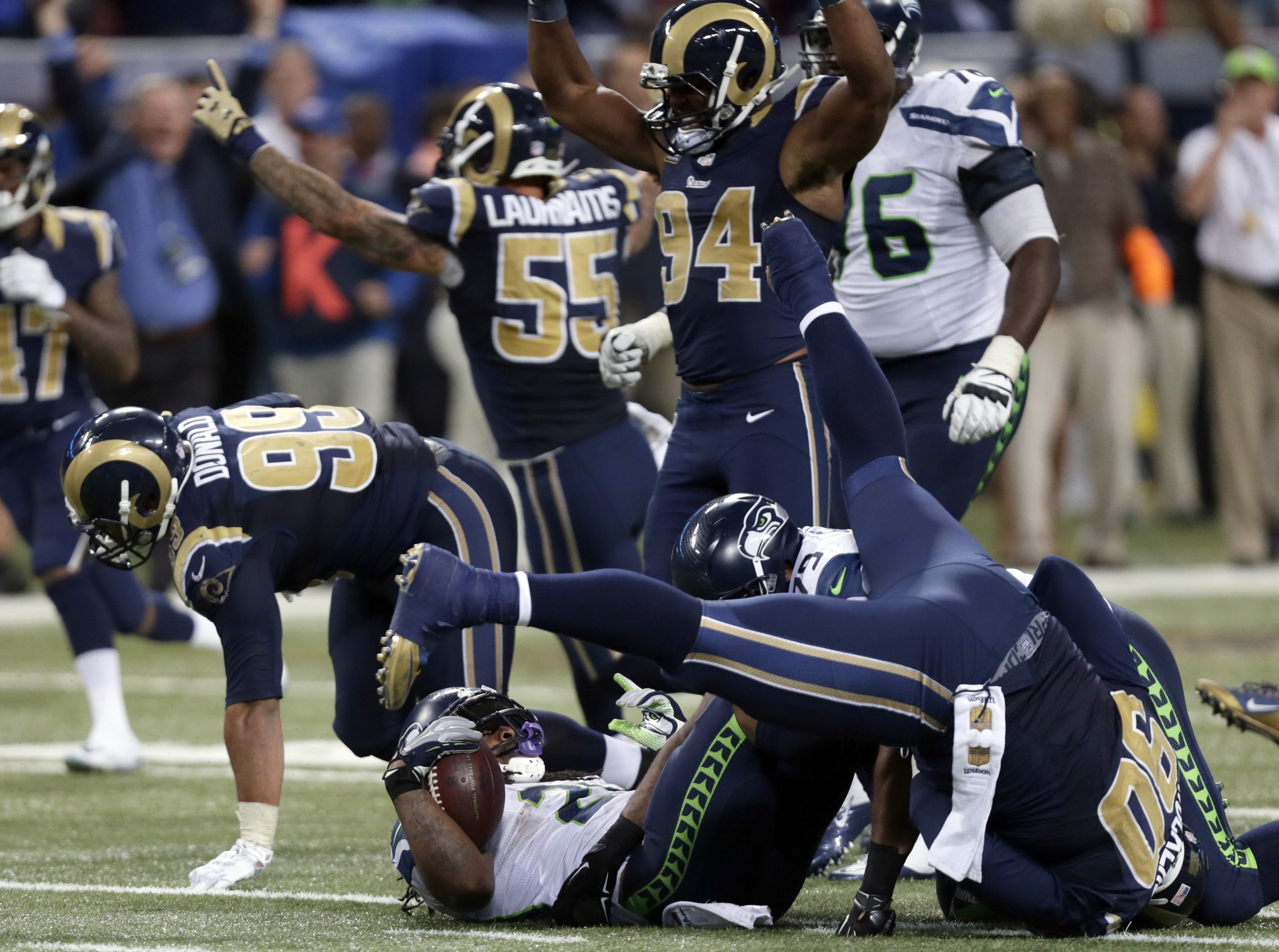 Seattle Seahawks running back Marshawn Lynch, bottom, lands on his back after being stopped on fourth down as St. Louis Rams players celebrate on the final play in overtime of an NFL football game Sunday, Sept. 13, 2015, in St. Louis. The Rams won 34-31.
