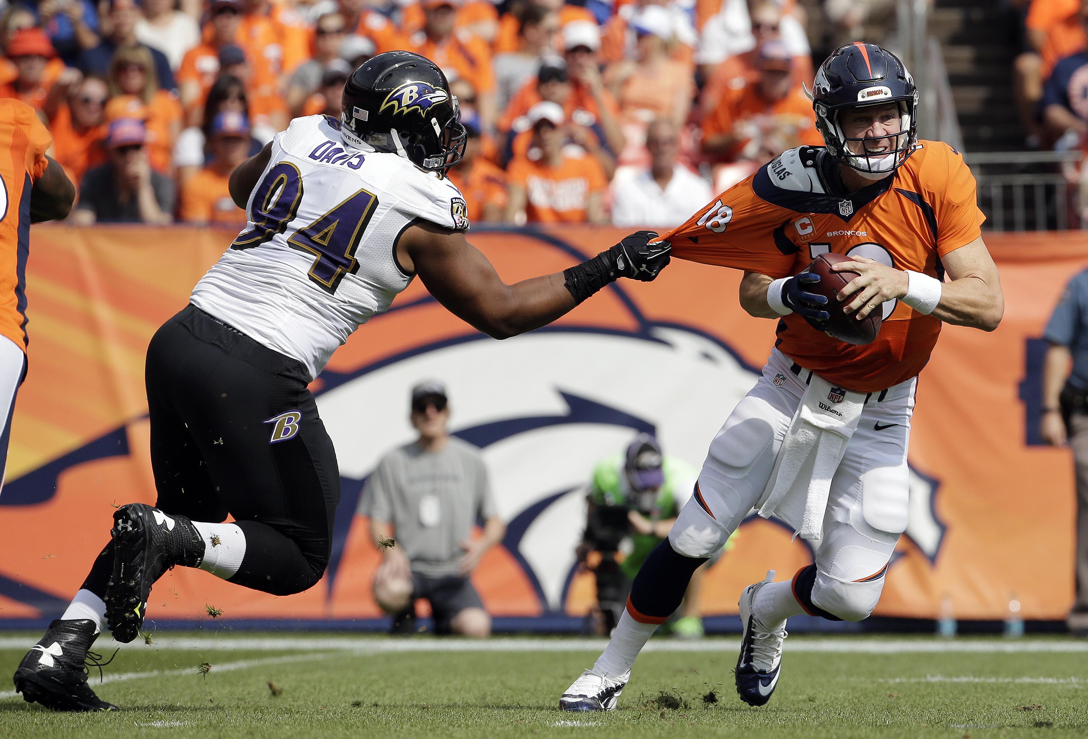 Baltimore Ravens defensive tackle Carl Davis, left, pulls on the jersey of Denver Broncos quarterback Peyton Manning during the first half of an NFL football game Sunday, Sept. 13, 2015, in Denver. (AP Photo/Jack Dempsey)