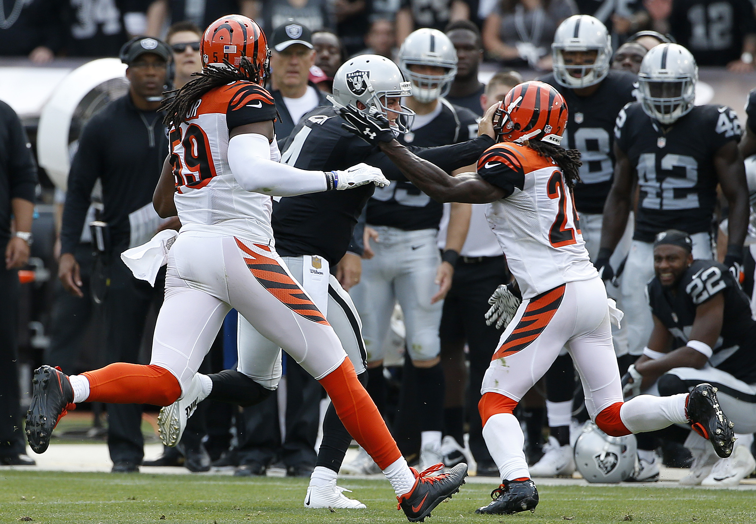 Oakland Raiders quarterback Derek Carr (4) stiff arms Cincinnati Bengals cornerback Adam Jones during the first half of an NFL football game in Oakland, Calif., Sunday, Sept. 13, 2015. The Bengals won 33-13. Carr was injured on the play and did not return
