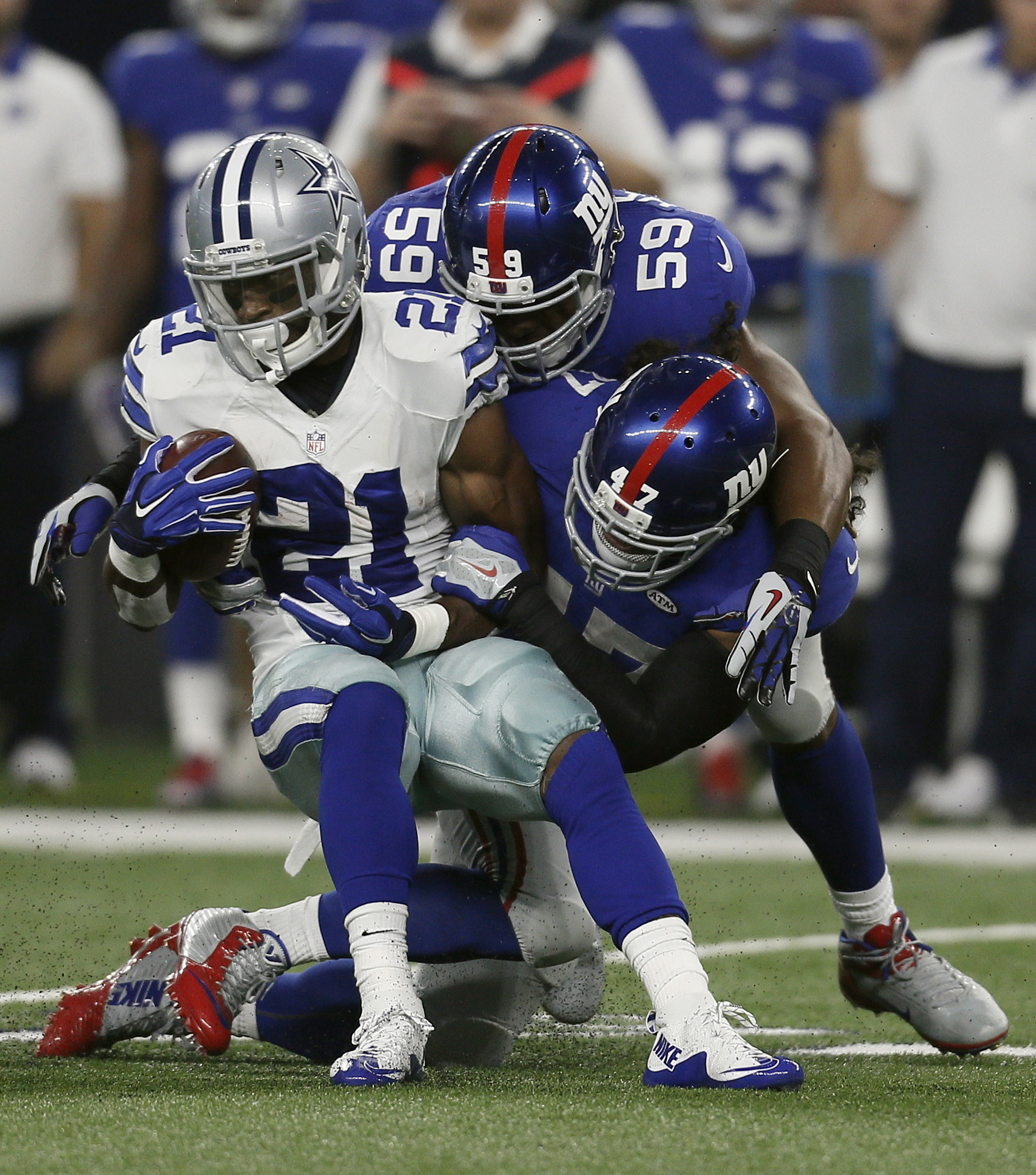 Dallas Cowboys running back Joseph Randle (21) is tackled by New York Giants outside linebacker Devon Kennard (59) and linebacker Uani' Unga (47) during the first half of an NFL football game Sunday, Sept. 13, 2015, in Arlington, Texas. (AP Photo/Brandon