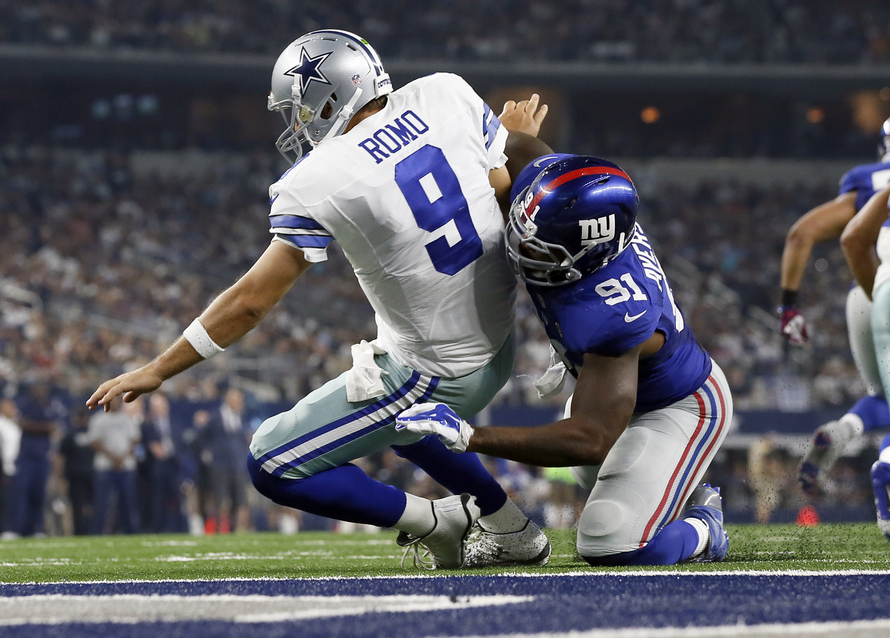 Dallas Cowboys quarterback Tony Romo (9) is sacked by New York Giants defensive end Robert Ayers (91) during the second half of an NFL football game Sunday, Sept. 13, 2015, in Arlington, Texas. (AP Photo/Tony Gutierrez)