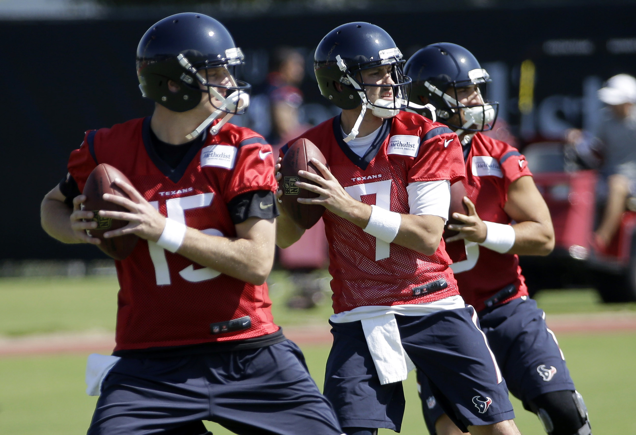FILE - In this June 1, 2015, file photo, Houston Texans quarterbacks, from left to right, Ryan Mallett, Brian Hoyer and Tom Savage drop back during an NFL football organized team activity in Houston. Hoyer was terrible in his Houston debut and was benched