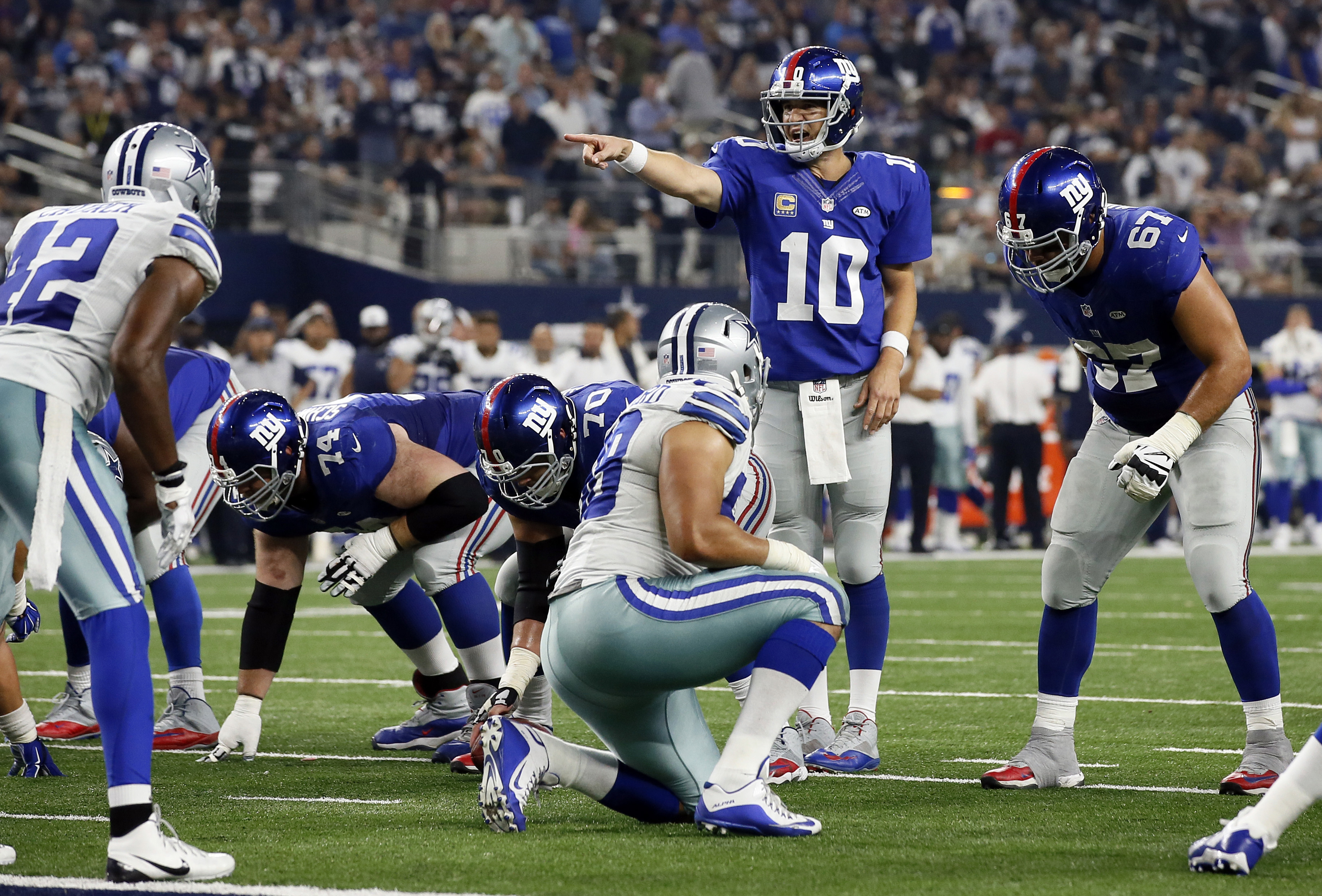 In this photo taken Sunday, Sept. 13, 2015, New York Giants quarterback Eli Manning (10) calls out at the line of scrimmage during the second half of an NFL football game against the Dallas Cowboys in Arlington, Texas. New York was about to put a damper o