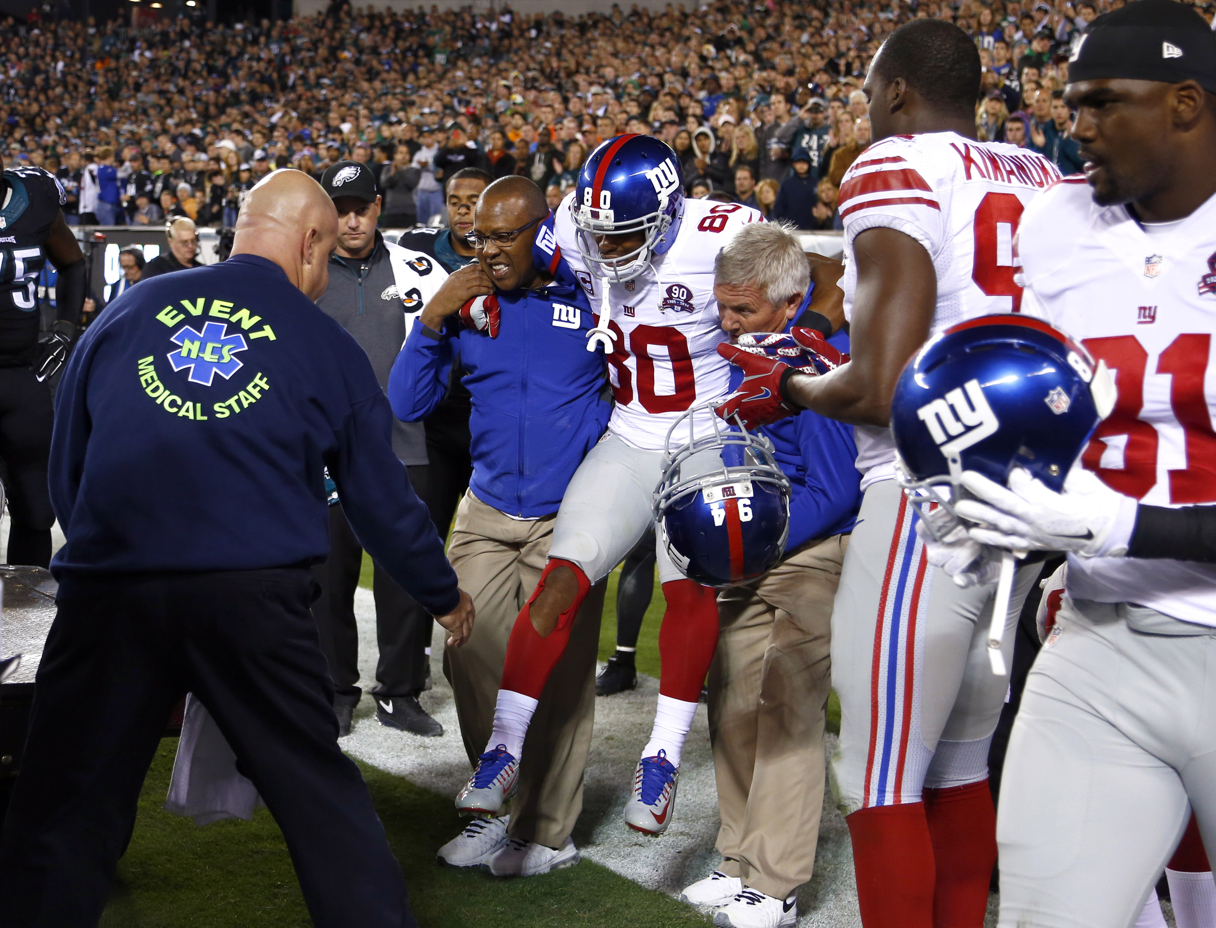 FILE - In this Oct. 12, 2014, file photo, New York Giants wide receiver Victor Cruz (80) is carried toward a cart after an injury during the second half of an NFL football game against the Philadelphia Eagles in Philadelphia. Sprains and strains. ACLs, MC