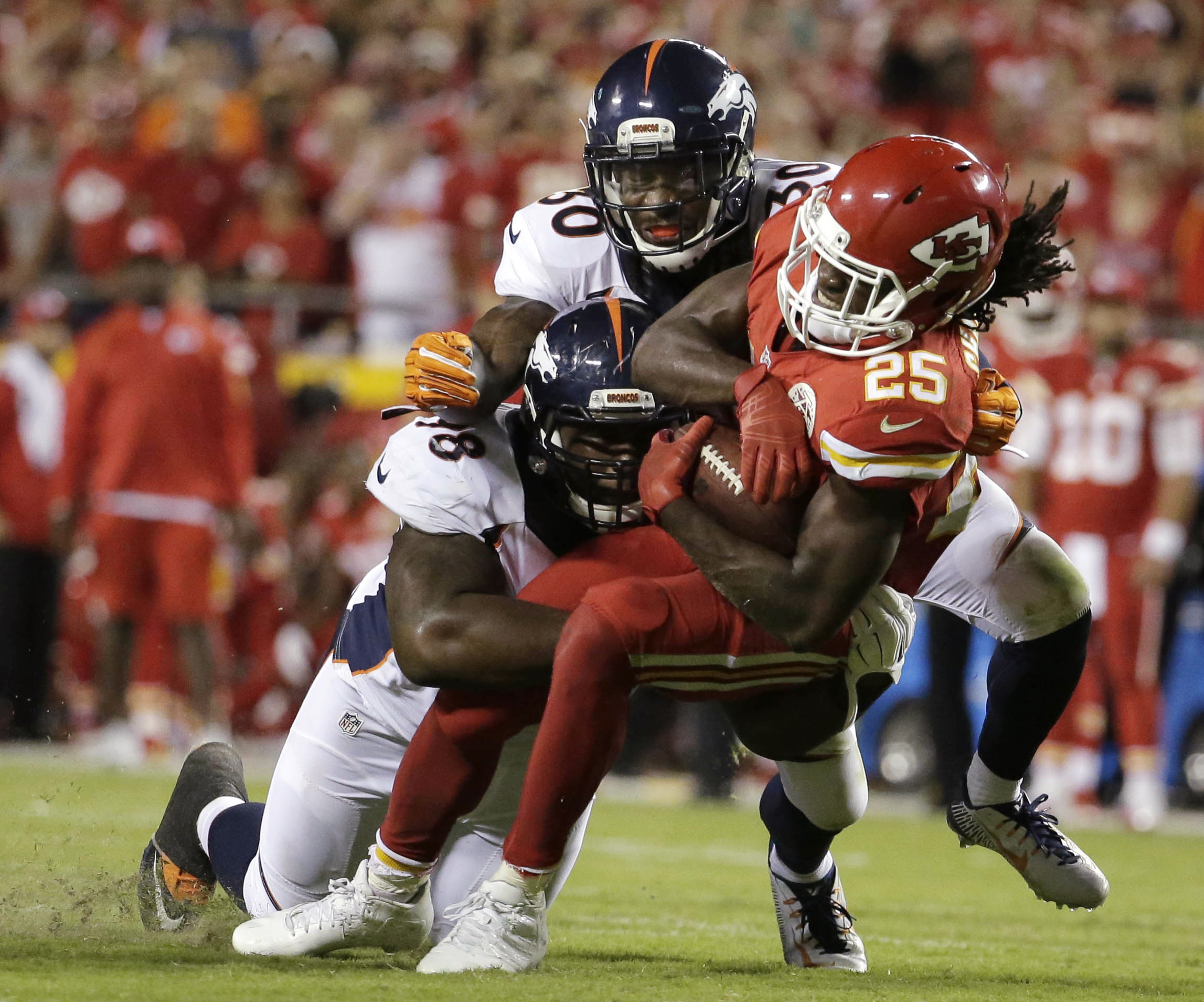 Kansas City Chiefs running back Jamaal Charles (25) is tackled by Denver Broncos nose tackle Darius Kilgo (98) and safety David Bruton Jr. (30) during the second half of an NFL football game in Kansas City, Mo., Thursday, Sept. 17, 2015. (AP Photo/Charlie