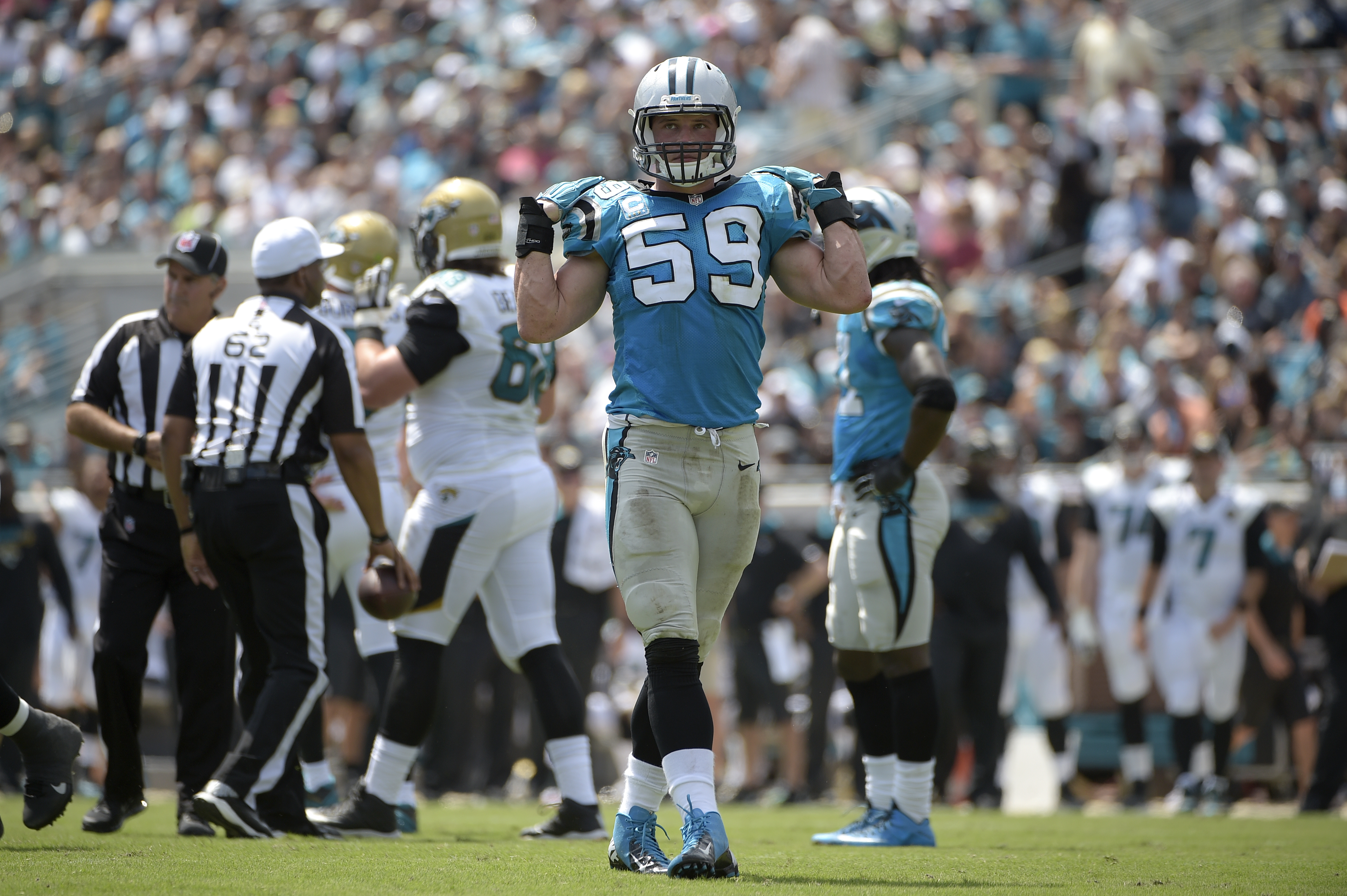 Carolina Panthers middle linebacker Luke Kuechly (59) adjusts his shoulder pads after making a tackle during the first half of an NFL football game against the Jacksonville Jaguars in Jacksonville, Fla., Sunday, Sept. 13, 2015. (AP Photo/Phelan M. Ebenhac