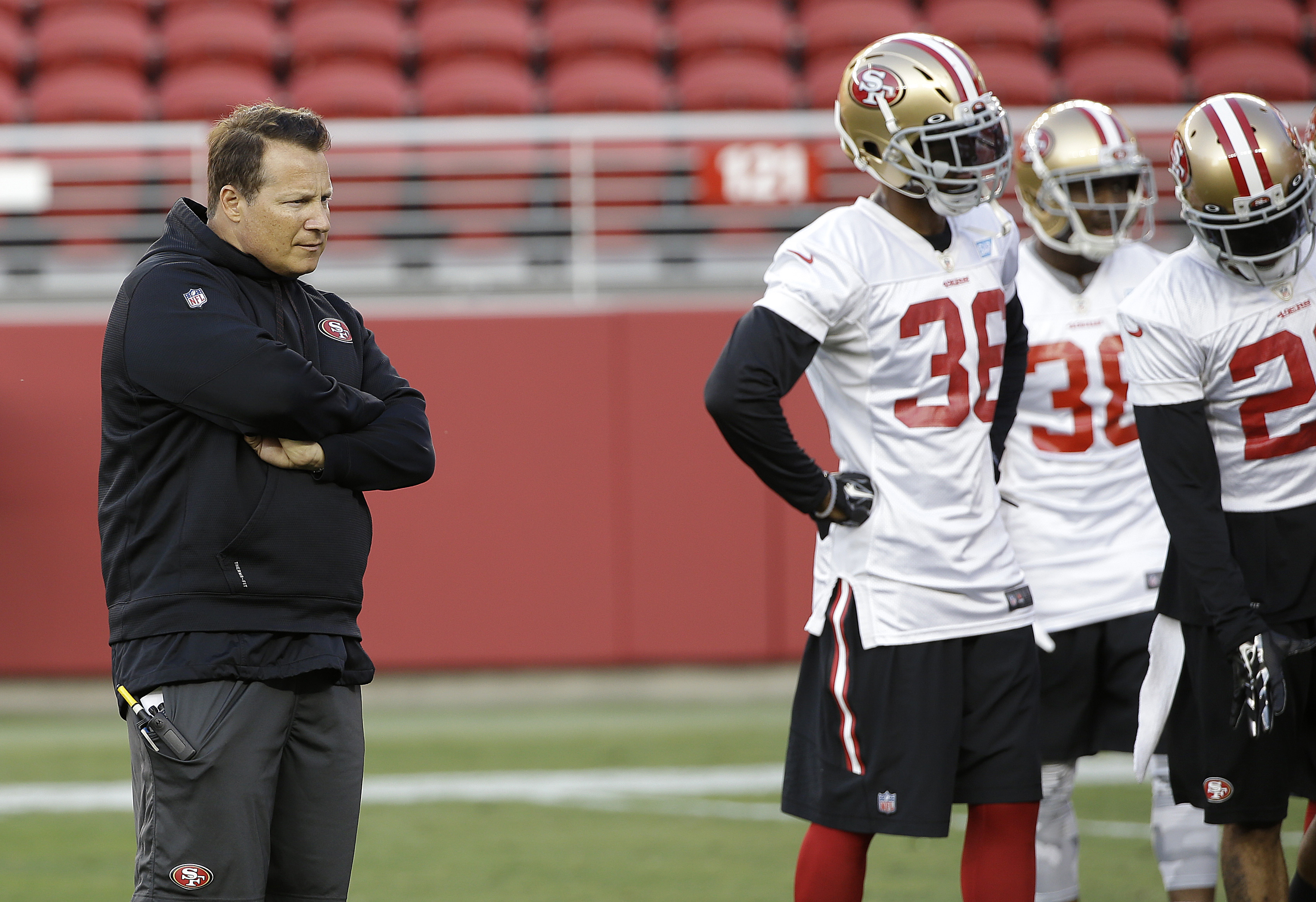 """FILE- In this Aug. 1, 2015, file photo, San Francisco 49ers defensive coordinator Eric Mangini, left, watches during  NFL football training camp in Santa Clara, Calif. Linebacker Michael Wilhoite calls him """"Mangenius."""" That nickname for 49ers defensive co"""