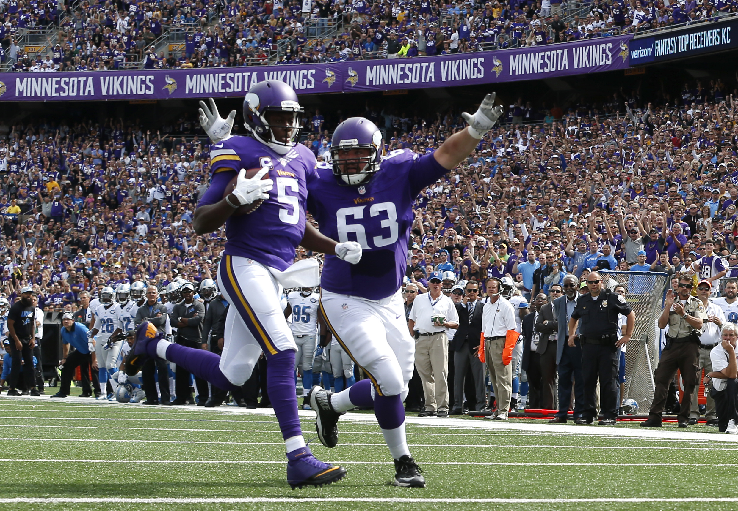 Minnesota Vikings quarterback Teddy Bridgewater (5) scores a touchdown against the Detroit Lions as Brandon Fusco (63) celebrates in the first half of an NFL football game in Minneapolis, Sunday, Sept. 20, 2015. (AP Photo/Jim Mone)