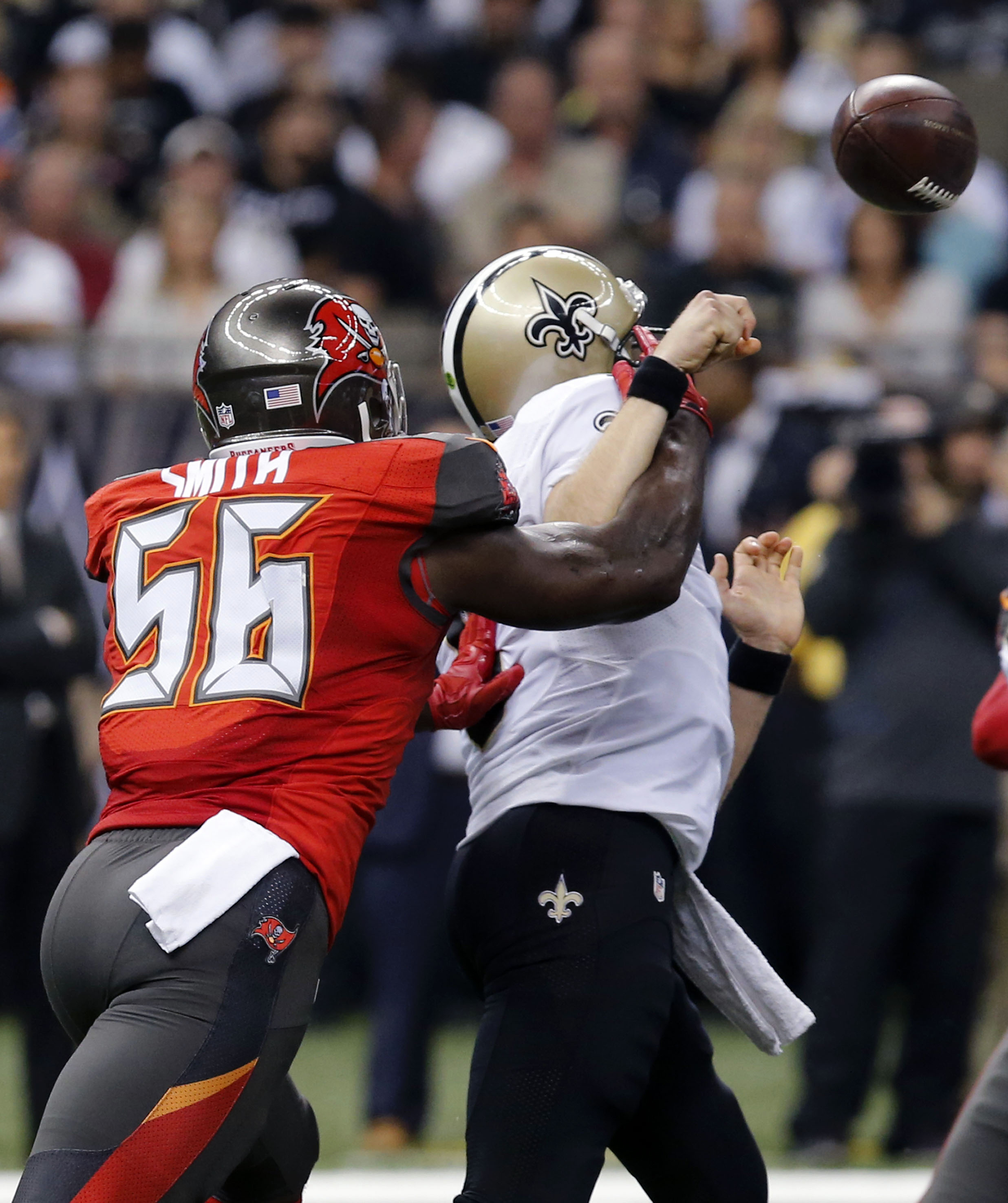 New Orleans Saints quarterback Drew Brees loses the football as he is hit by Tampa Bay Buccaneers defensive end Jacquies Smith (56) in the first half of an NFL football game in New Orleans, Sunday, Sept. 20, 2015. (AP Photo/Bill Haber)
