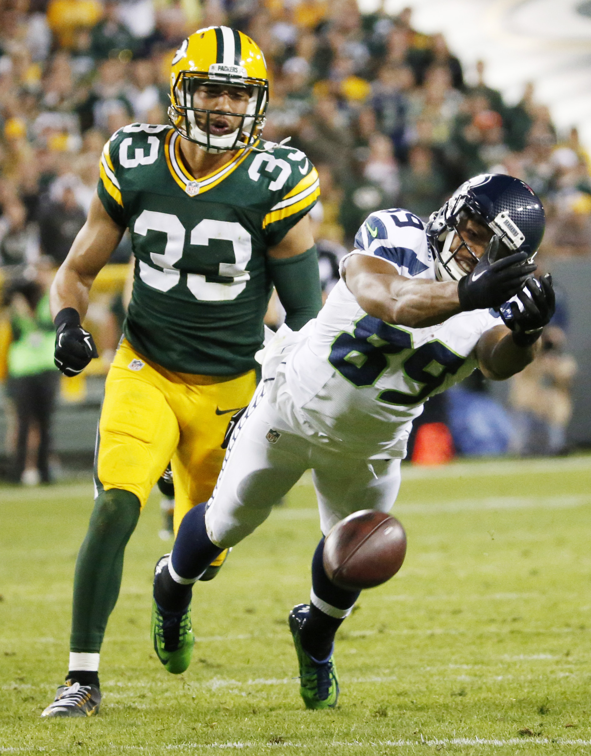 Seattle Seahawks' Doug Baldwin can't catch a pass in front of Green Bay Packers' Micah Hyde (33) during the second half of an NFL football game Sunday, Sept. 20, 2015, in Green Bay, Wis. (AP Photo/Mike Roemer)
