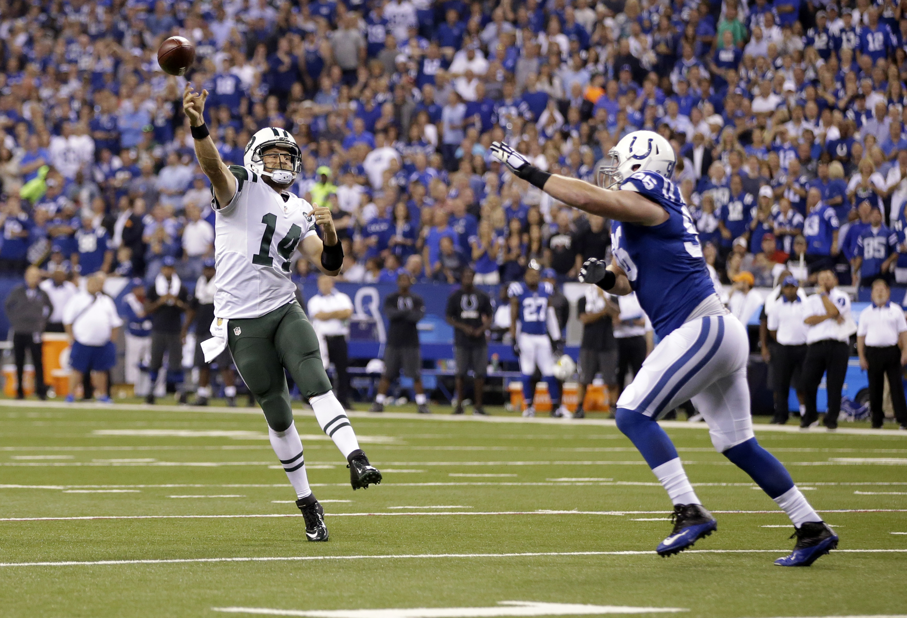 New York Jets quarterback Ryan Fitzpatrick (14) throws for a touchdown over Indianapolis Colts defensive end Henry Anderson (96) in the first half of an NFL football game in Indianapolis, Monday, Sept. 21, 2015. (AP Photo/Darron Cummings)