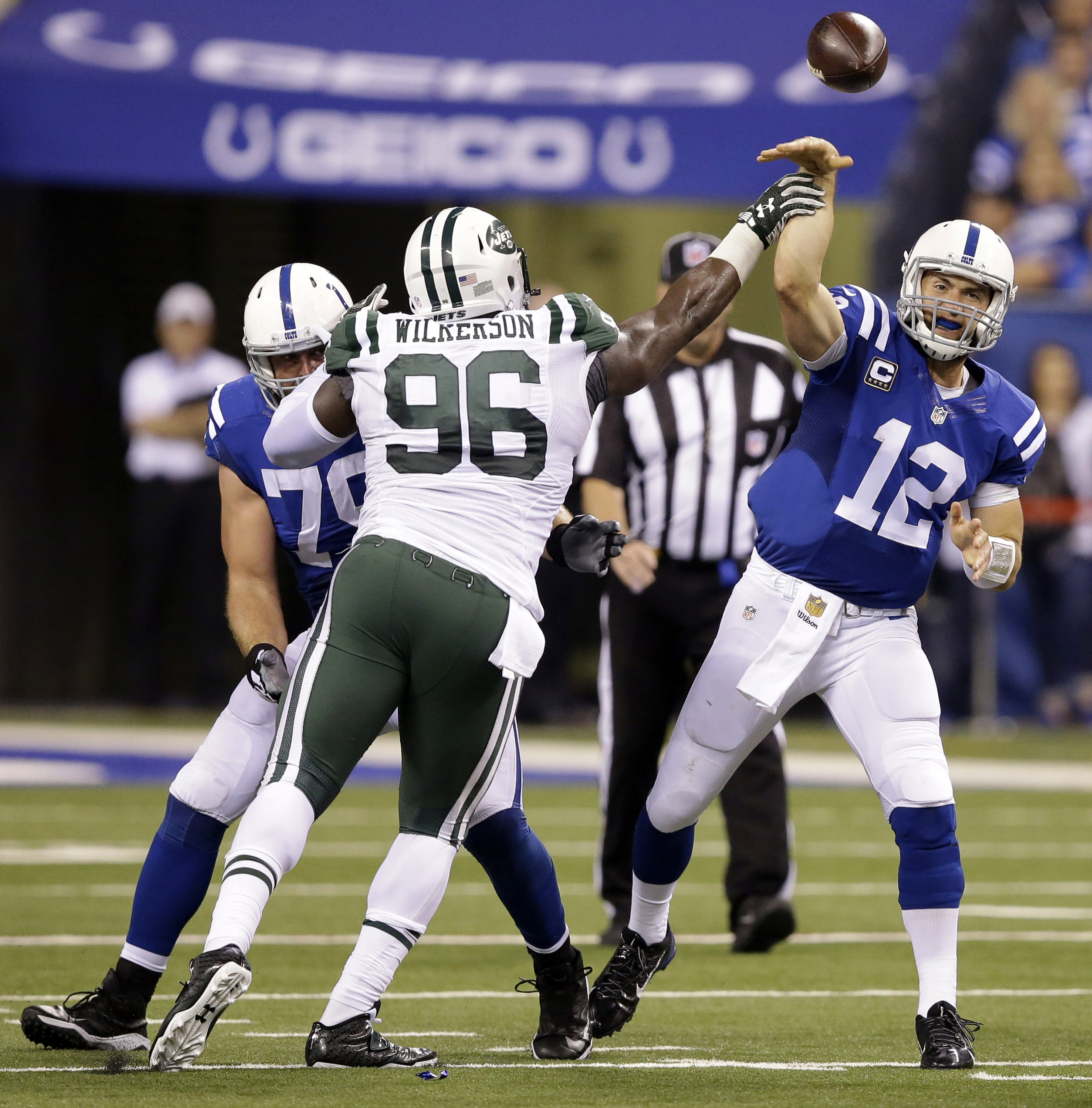 Indianapolis Colts quarterback Andrew Luck (12) is hit by New York Jets defensive end Muhammad Wilkerson (96) as he throws during the second half of an NFL football game in Indianapolis, Monday, Sept. 21, 2015. (AP Photo/Darron Cummings)