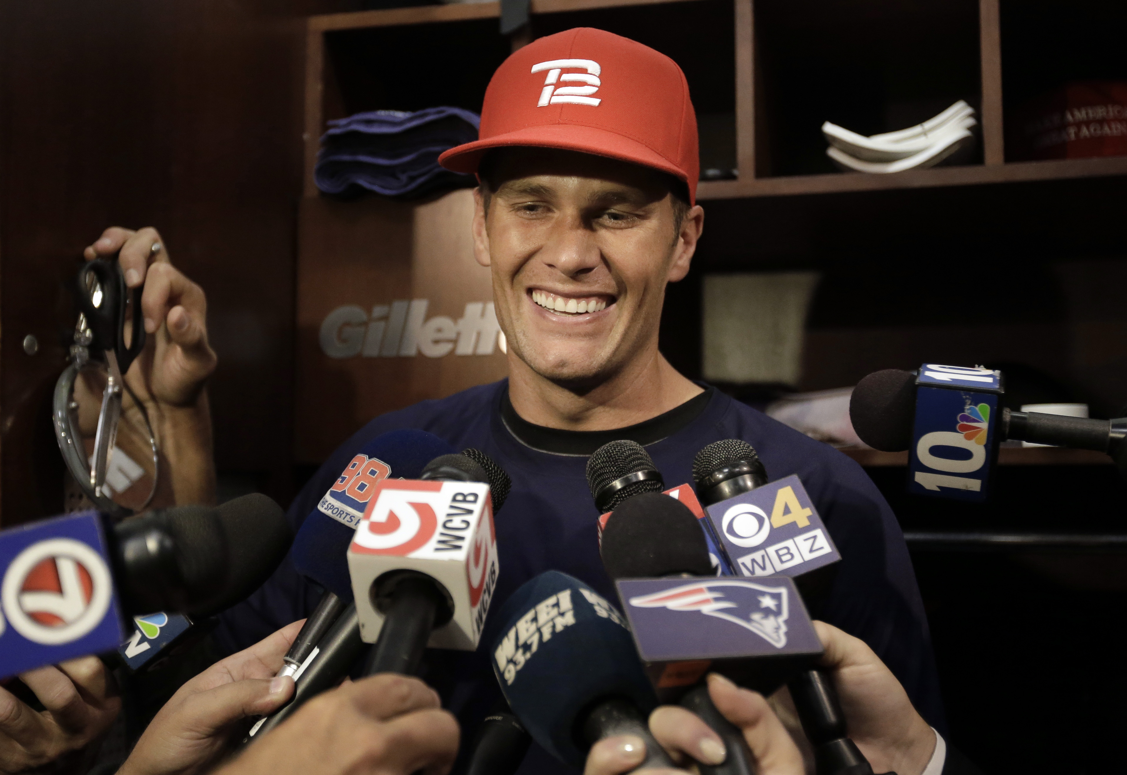 New England Patriots quarterback Tom Brady smiles while speaking with reporters in the locker room at Gillette Stadium before an NFL football practice, Wednesday, Sept. 23, 2015, in Foxborough, Mass. (AP Photo/Steven Senne)