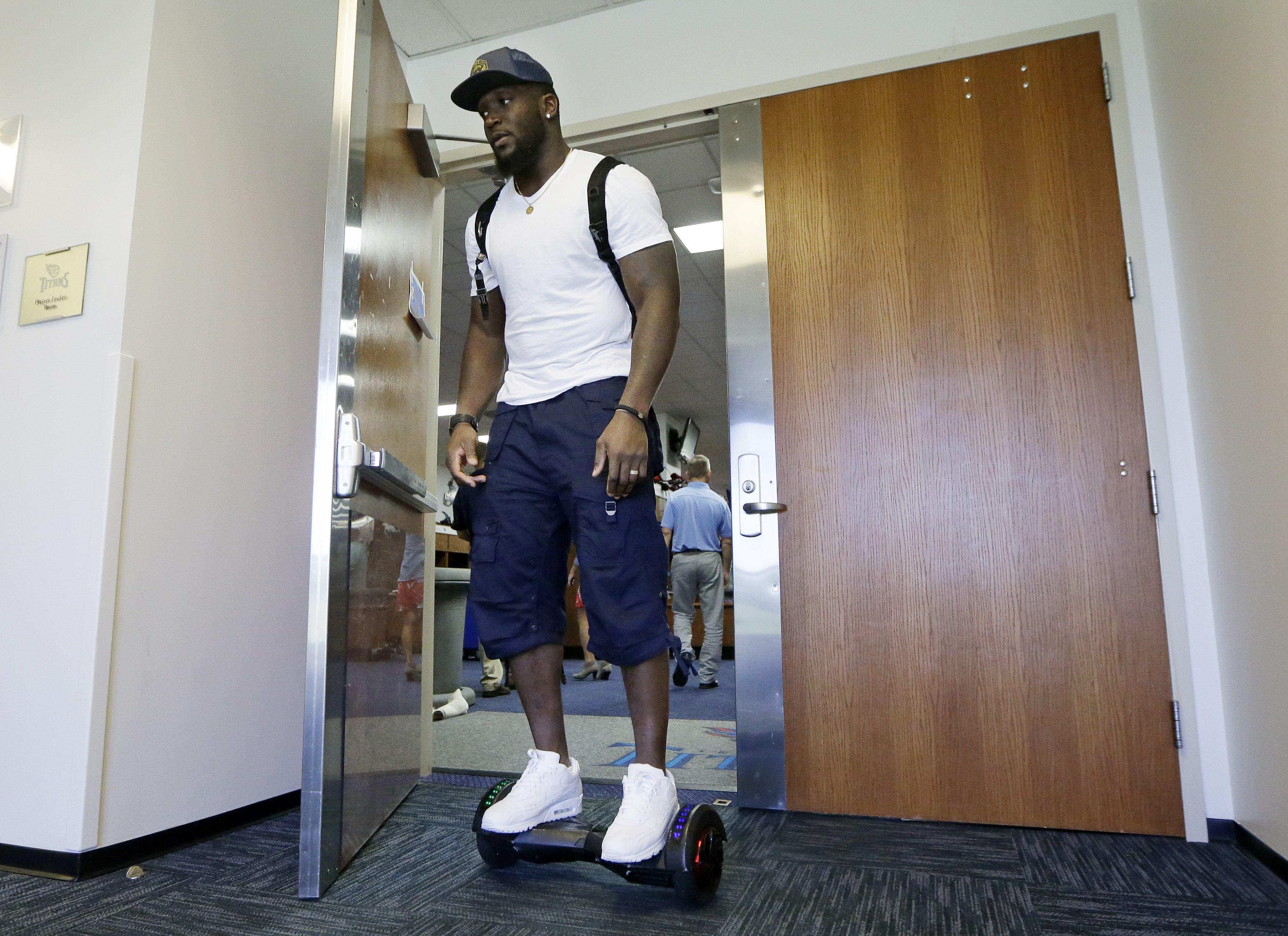 In this Wednesday, Sept. 23, 2015, photo, Tennessee Titans linebacker Brian Orakpo leaves the locker room on a motorized skateboard in Nashville, Tenn. Many of the Titans players use the devices to travel through the team's facility. (AP Photo/Mark Humphr
