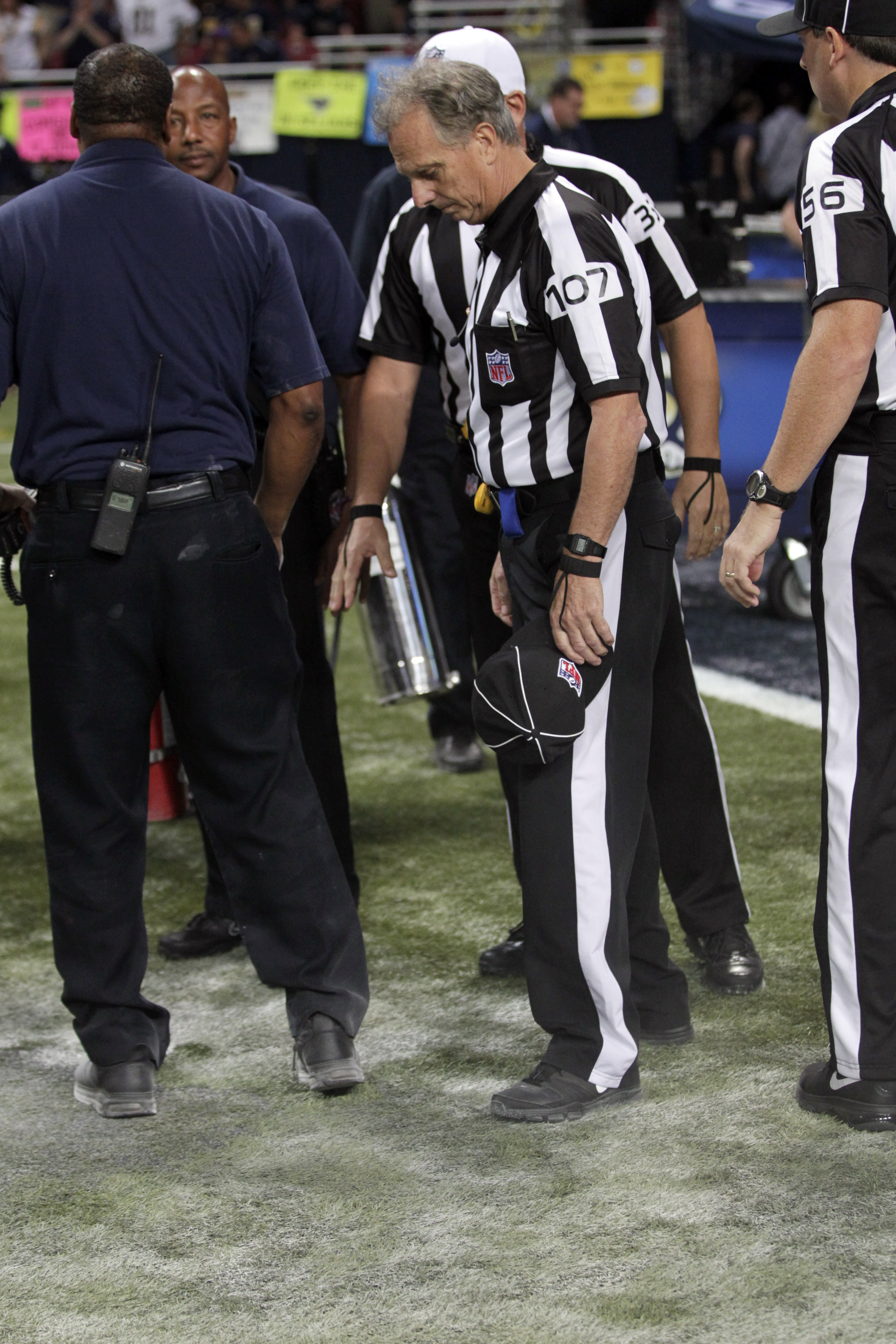 Line judge Ron Marinucci looks over a section of charred turf burned during pyrotechnics before an NFL football game between the St. Louis Rams and the Pittsburgh Steelers, Sunday, Sept. 27, 2015, in St. Louis. (AP Photo/Tom Gannam)