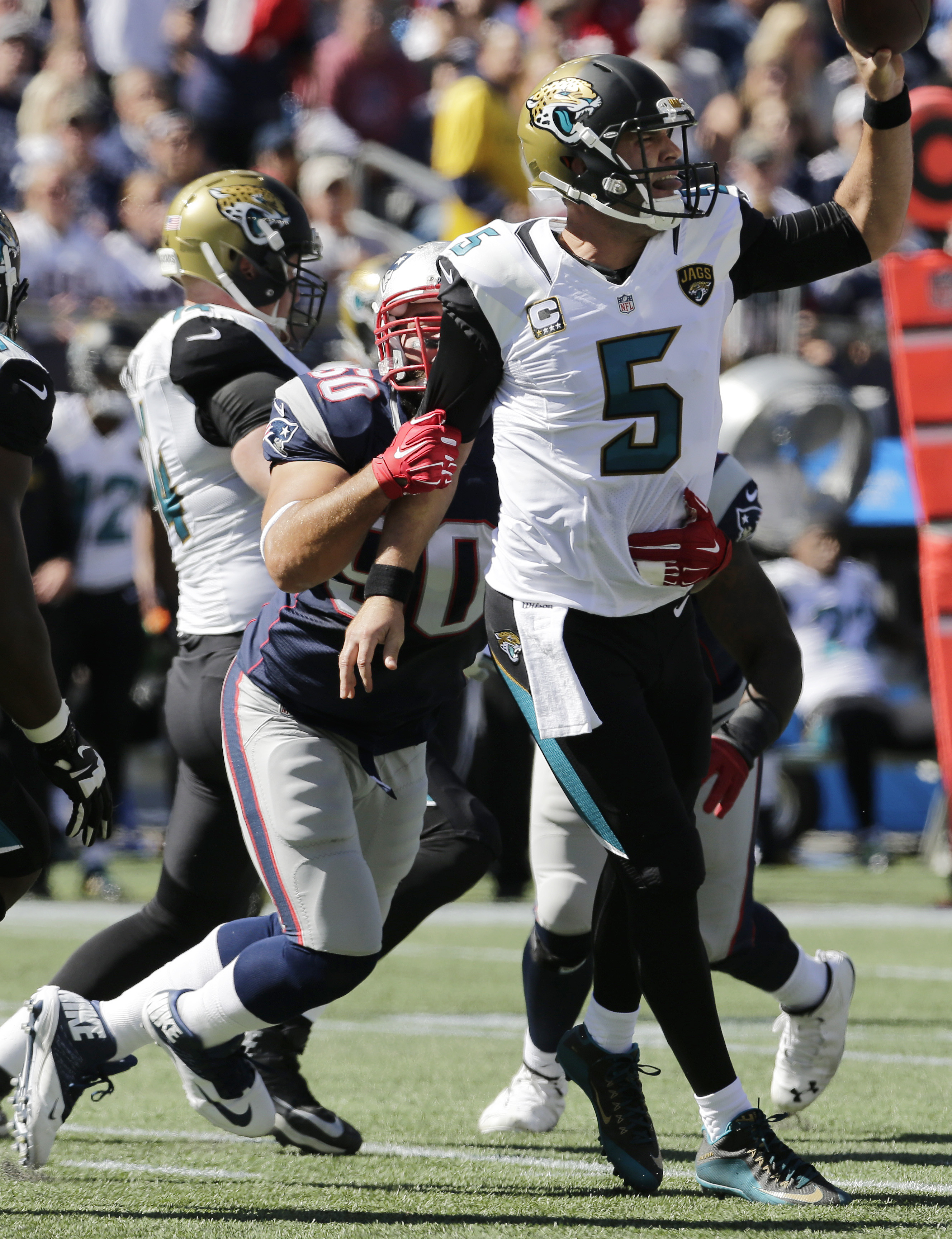 Jacksonville Jaguars quarterback Blake Bortles (5) tosses the ball with his left hand as New England Patriots defensive end Rob Ninkovich (50) wraps him up in the first half of an NFL football game, Sunday, Sept. 27, 2015, in Foxborough, Mass. (AP Photo/C