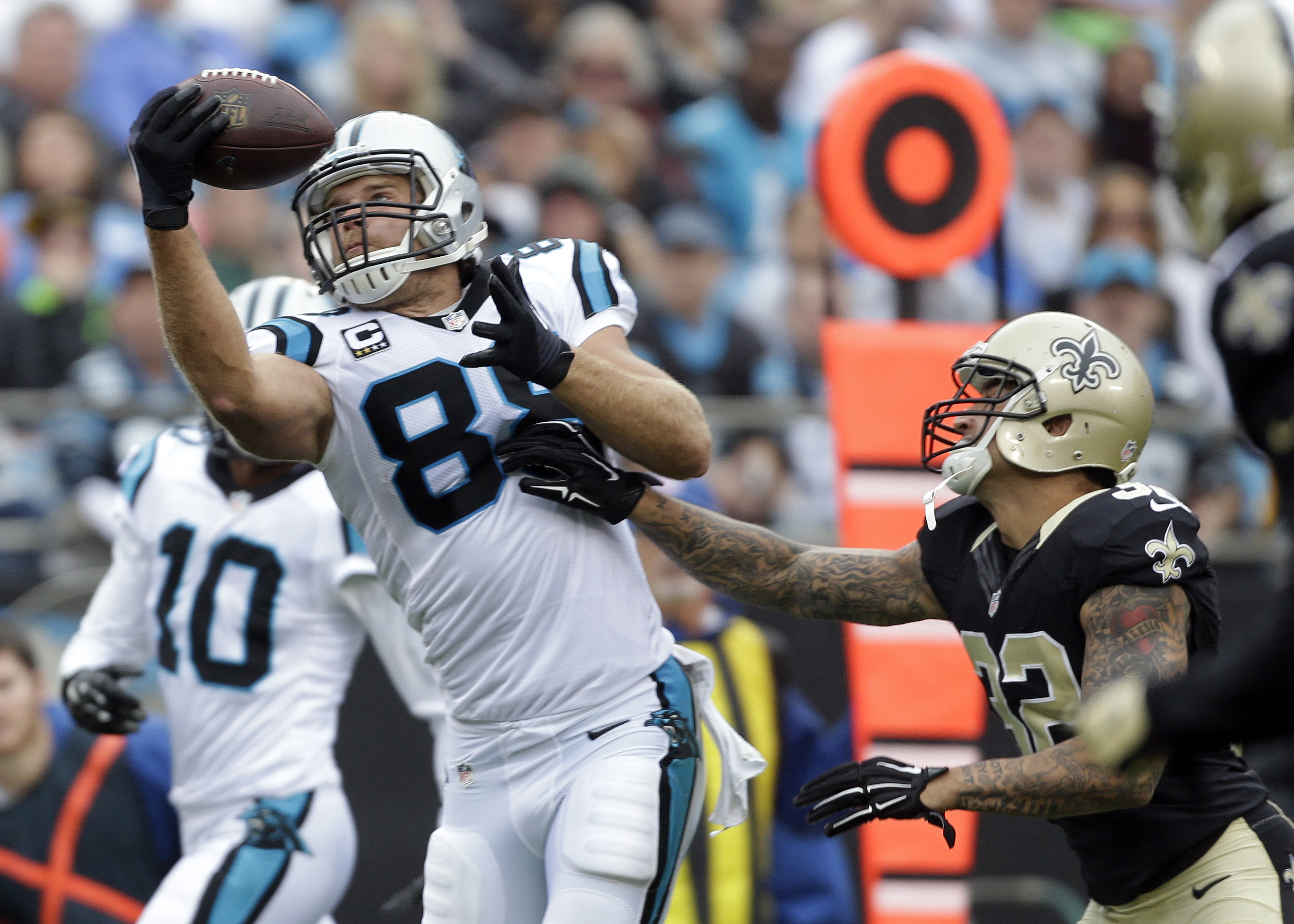 Carolina Panthers' Greg Olsen (88) catches a pass as New Orleans Saints' Kenny Vaccaro (32) defends in the first half of an NFL football game in Charlotte, N.C., Sunday, Sept. 27, 2015. (AP Photo/Bob Leverone)