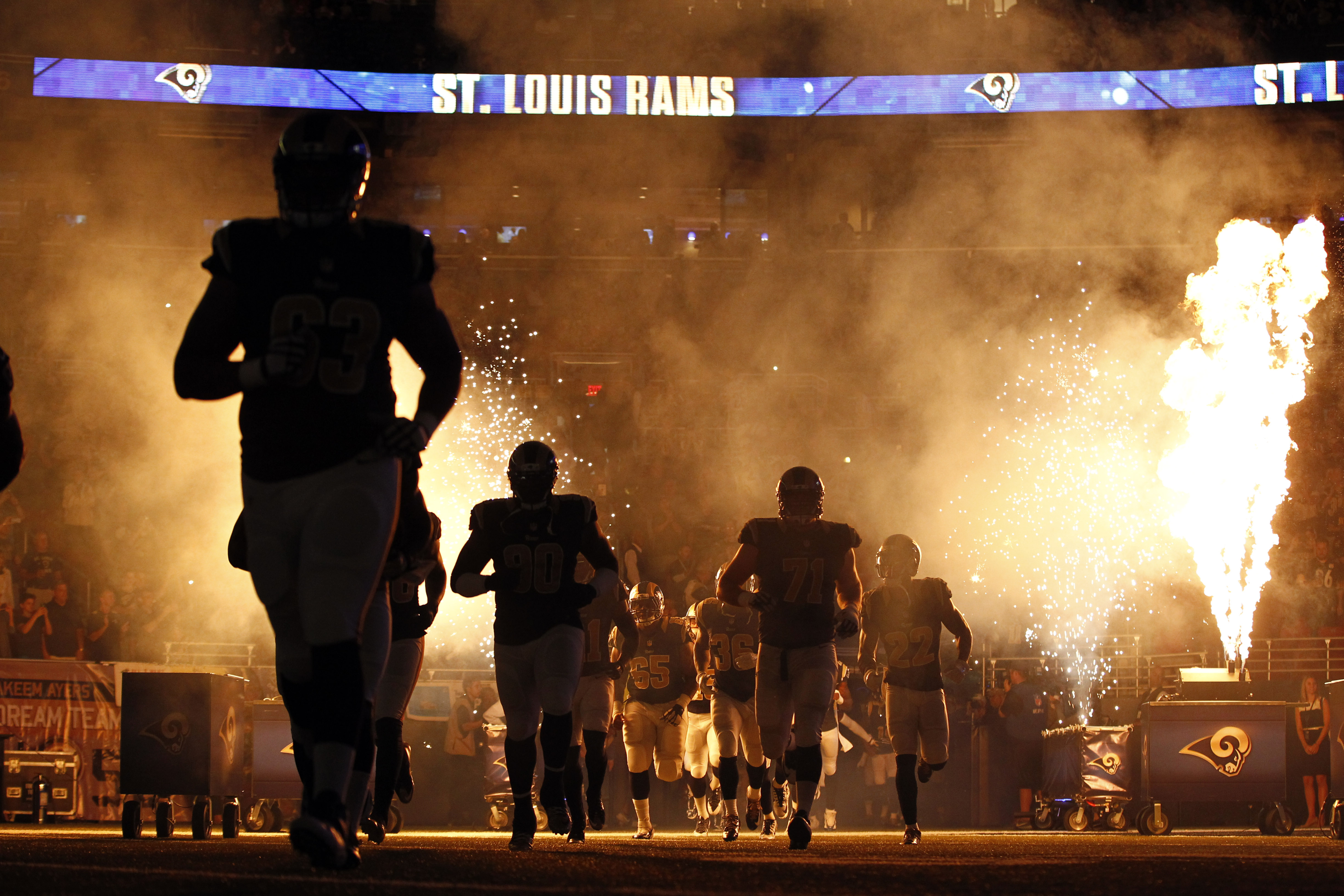 Members of the St. Louis Rams run on the field before an NFL football game against the Pittsburgh Steelers, Sunday, Sept. 27, 2015, in St. Louis. The game was delayed because part of the pyrotechnics used during the introductions briefly caught the turf o