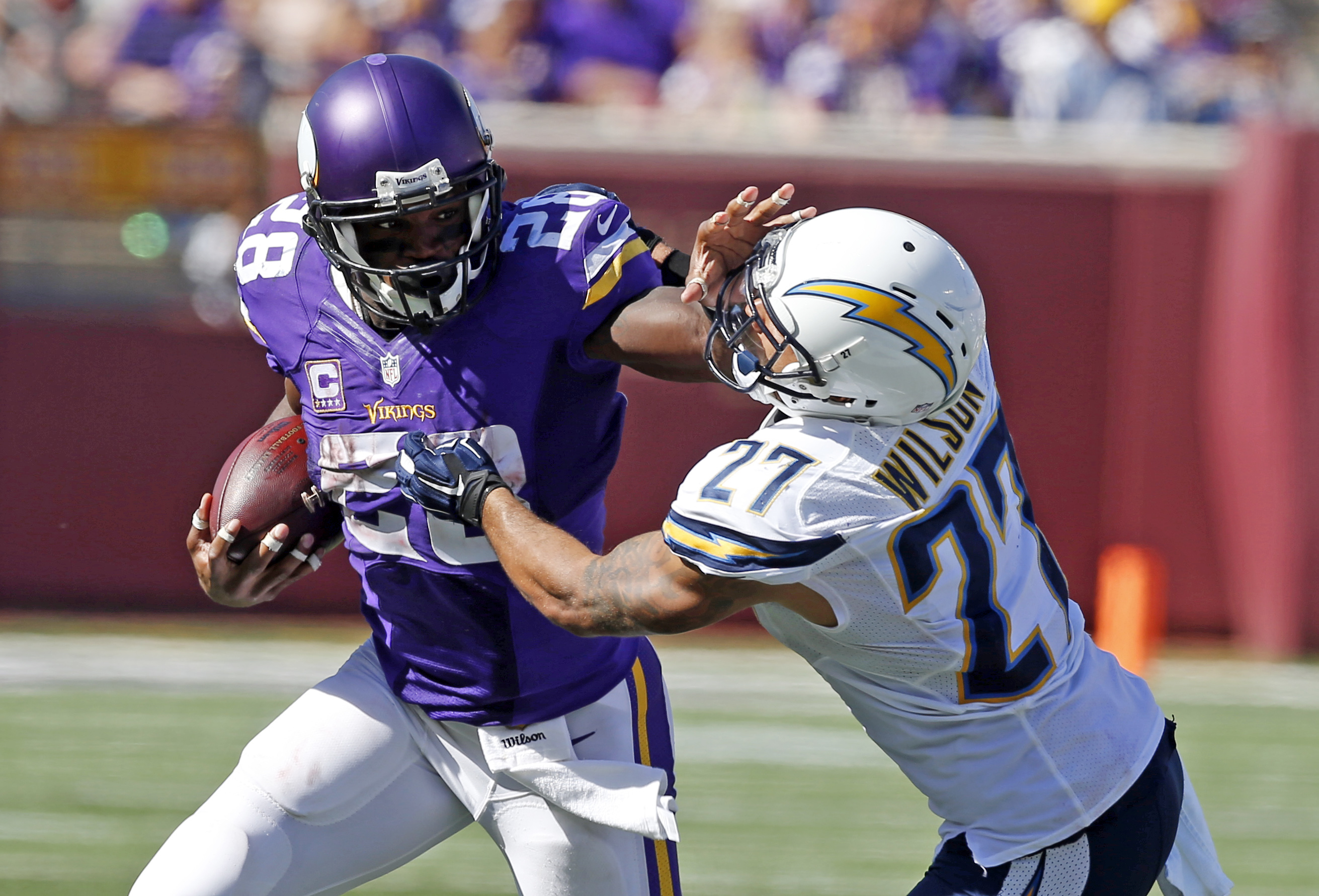Minnesota Vikings running back Adrian Peterson (28) pushes off the tackle of San Diego Chargers strong safety Jimmy Wilson (27) on his way to a touchdown in the second half of an NFL football game in Minneapolis, Sunday, Sept. 27, 2015. (AP Photo/Jim Mone