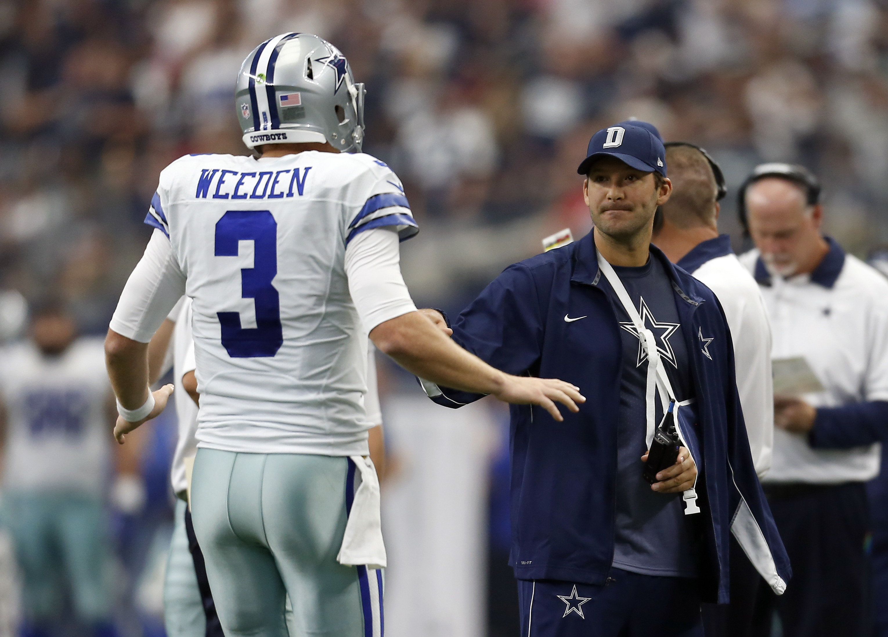 Dallas Cowboys quarterback Brandon Weeden (3) is greeted on the sideline by quarterback Tony Romo, right, in the first half of an NFL football game on Sunday, Sept. 27, 2015, in Arlington, Texas. (AP Photo/Brandon Wade)