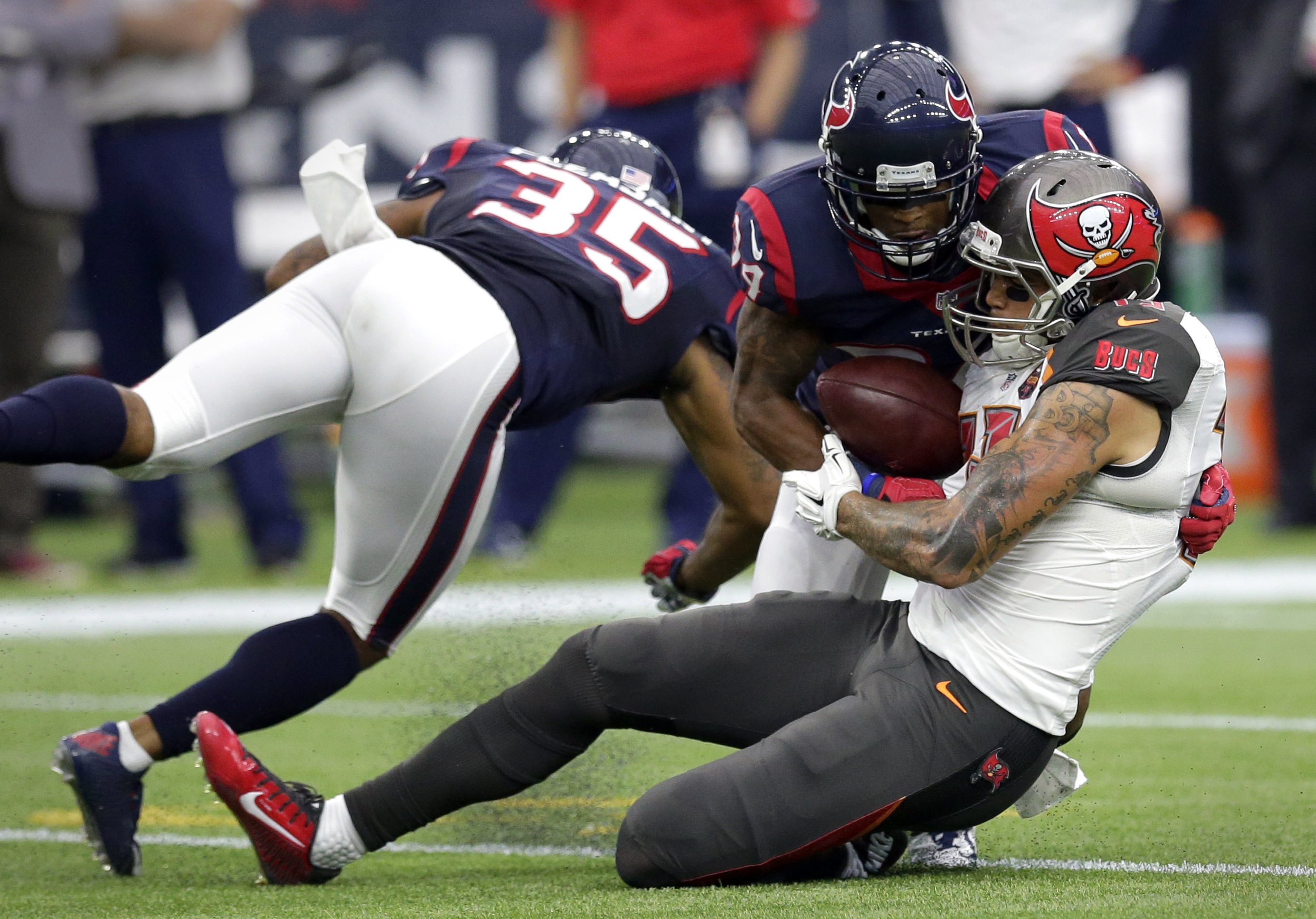 Houston Texans' Eddie Pleasant (35) and A.J. Bouye (34) break up a pass intended for Tampa Bay Buccaneers' Mike Evans, right, during the second half of an NFL football game Sunday, Sept. 27, 2015, in Houston. (AP Photo/David J. Phillip)