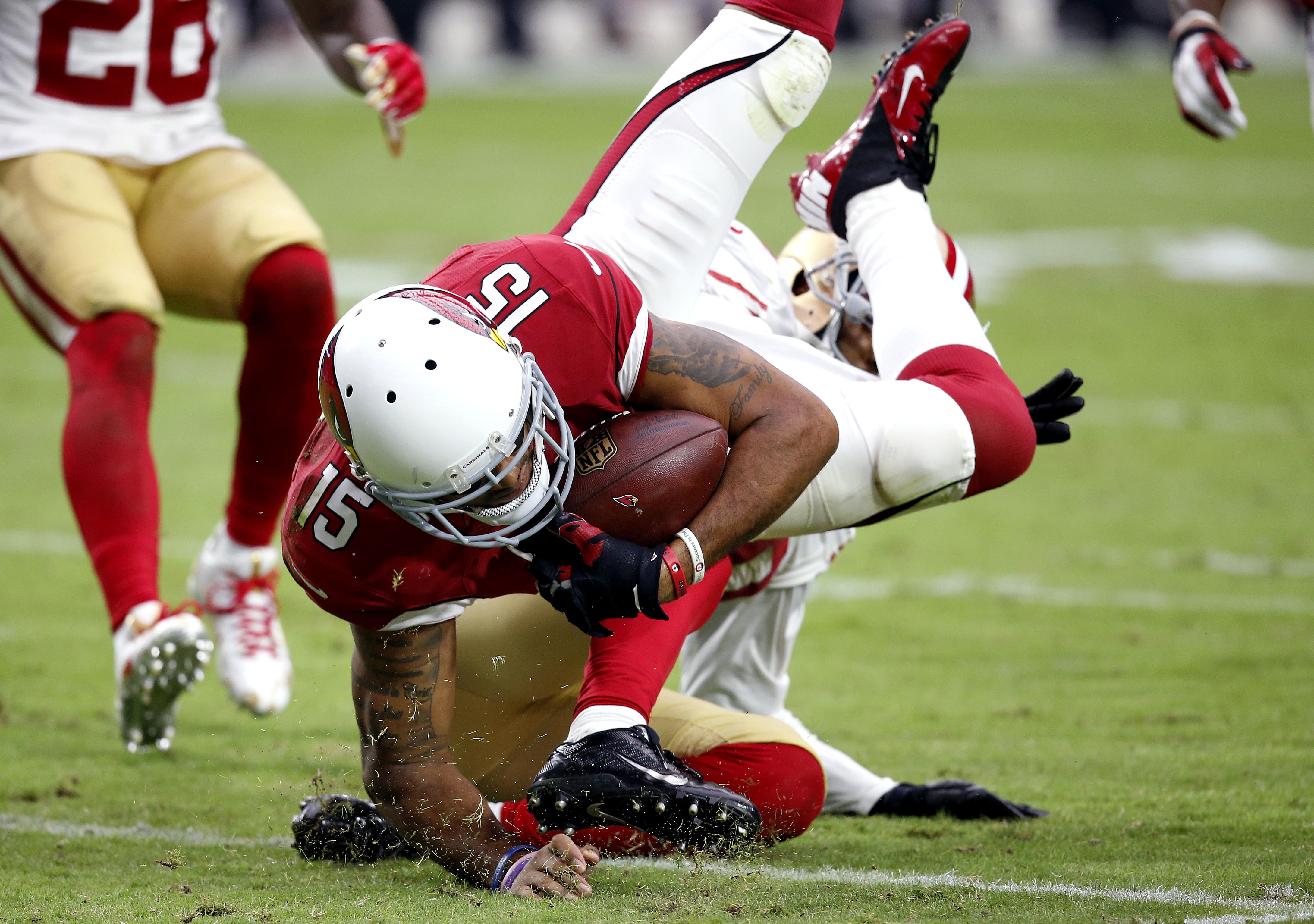 Arizona Cardinals wide receiver Michael Floyd (15) is tackled by San Francisco 49ers cornerback Kenneth Acker during the first half of an NFL football game, Sunday, Sept. 27, 2015, in Glendale, Ariz.  (AP Photo/Ross D. Franklin)
