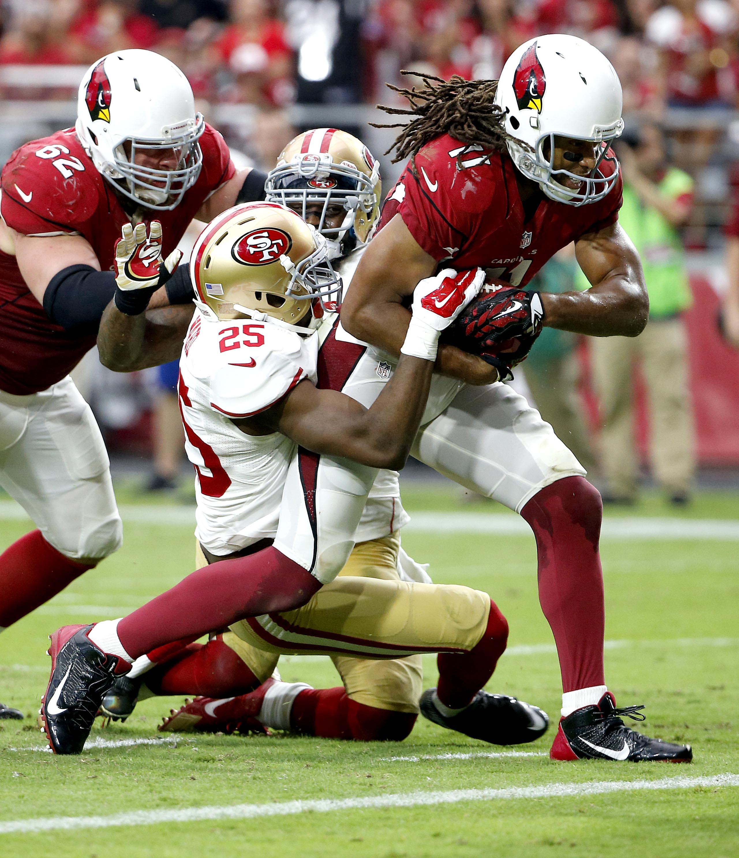 Arizona Cardinals wide receiver Larry Fitzgerald (11) scores a touchdown as San Francisco 49ers strong safety Jimmie Ward (25) defends during the second half of an NFL football game, Sunday, Sept. 27, 2015, in Glendale, Ariz.  (AP Photo/Ross D. Franklin)
