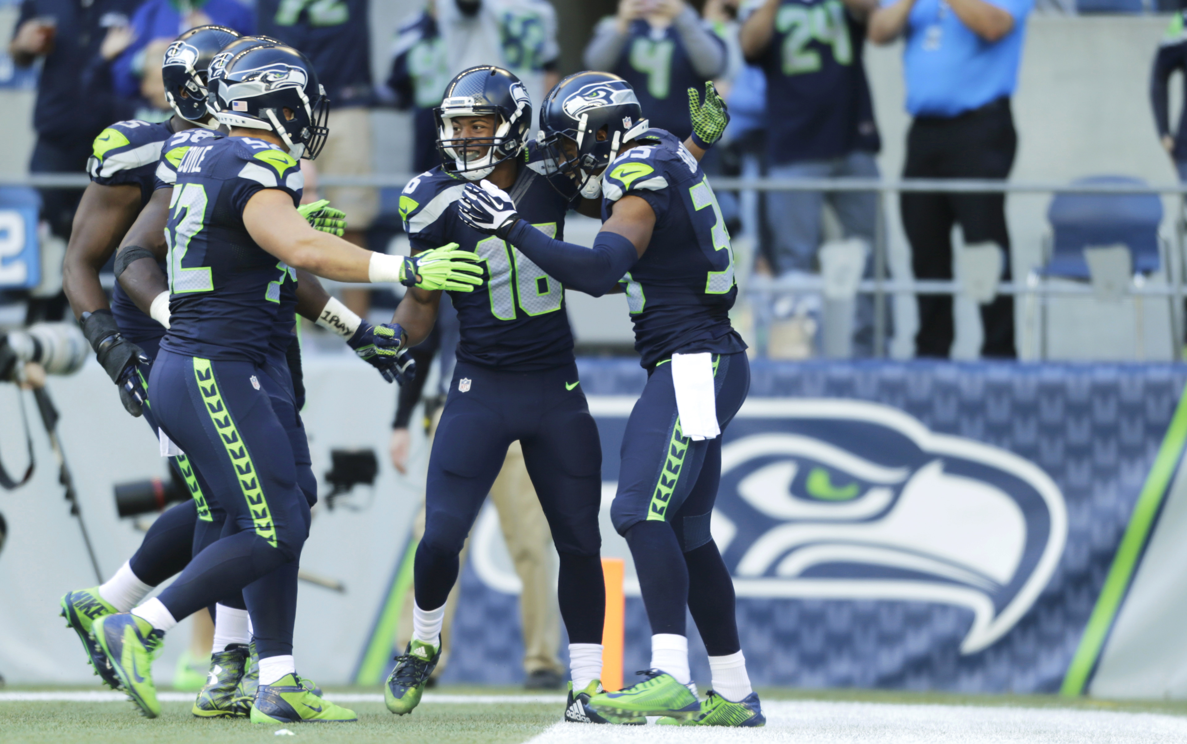 Seattle Seahawks wide receiver Tyler Lockett, second from right, is greeted by teammates, including DeShawn Shead, right, after returning a Chicago Bears kickoff 105 yards for a touchdown in the second half of an NFL football game, Sunday, Sept. 27, 2015,
