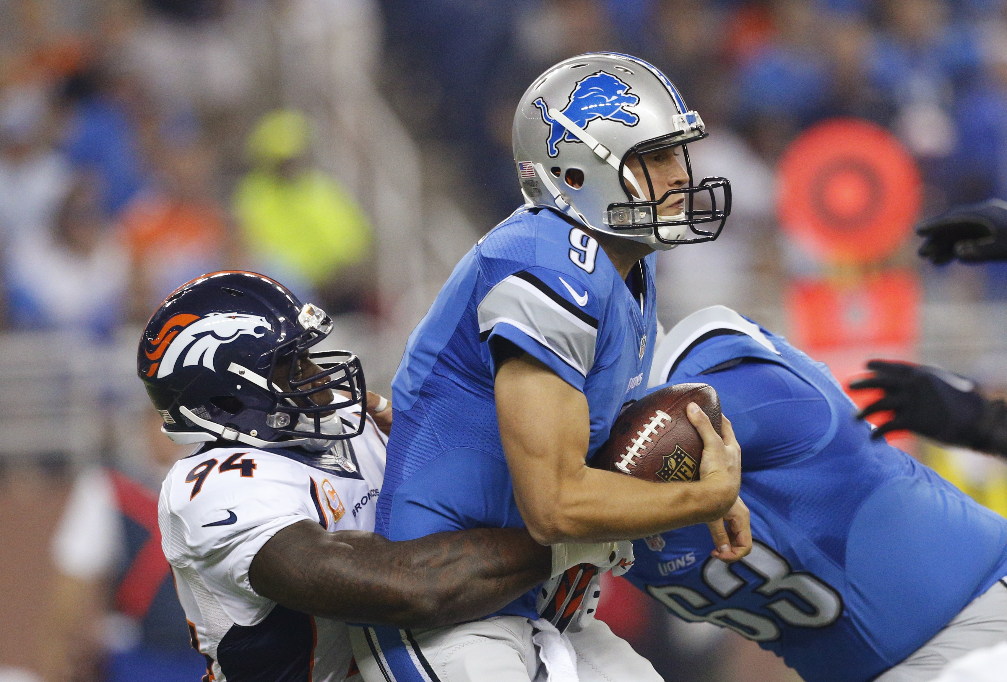 Detroit Lions quarterback Matthew Stafford is sacked by Denver Broncos outside linebacker DeMarcus Ware (94) during the first half of an NFL football game, Sunday, Sept. 27, 2015, in Detroit. (AP Photo/Rick Osentoski)