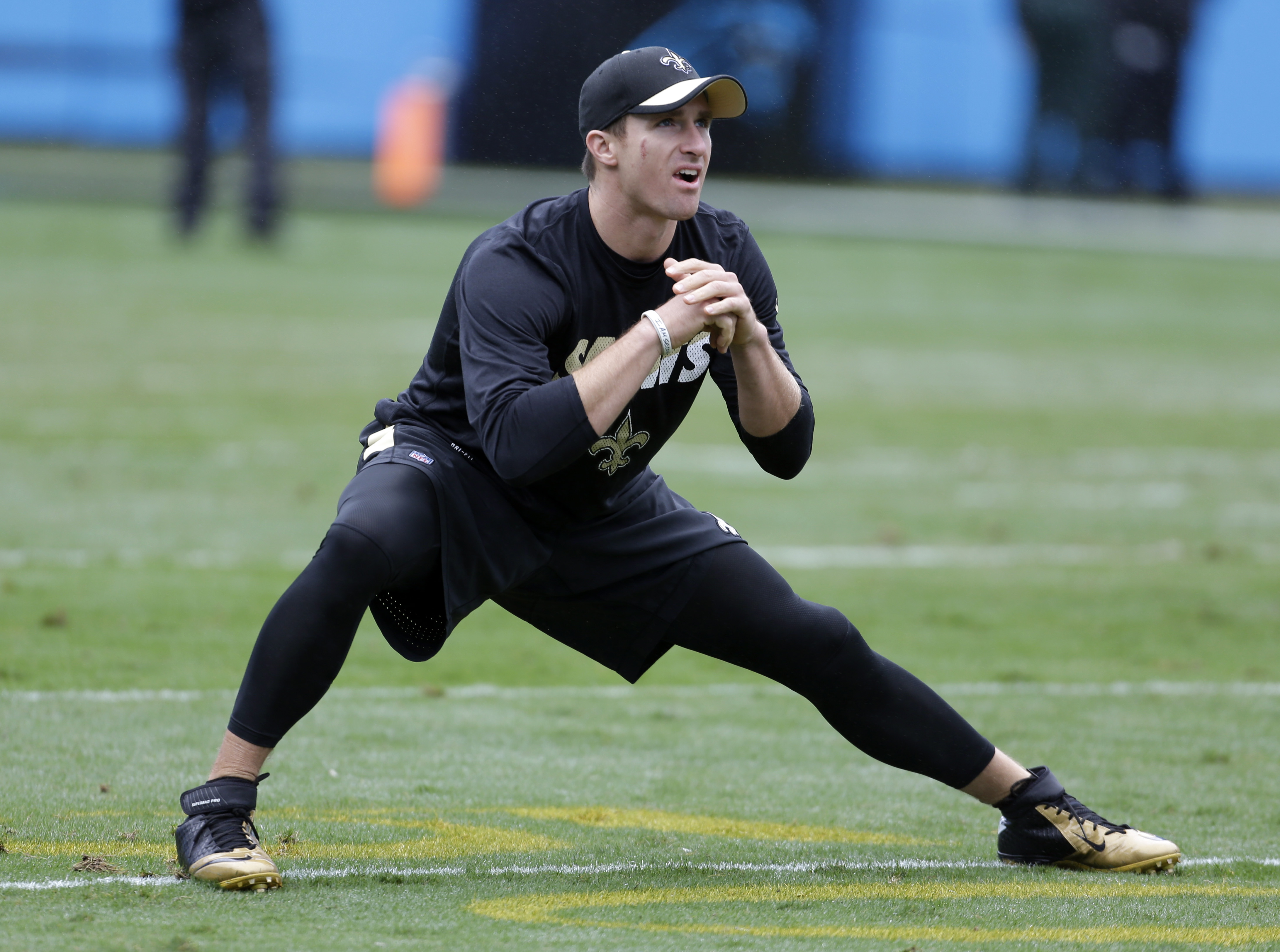 FILE - In this Sept. 27, 2015, file photo, New Orleans Saints' Drew Brees stretches before an NFL football game against the Carolina Panthers in Charlotte, N.C. Brees is trying to work his way back into the lineup after missing last week's game with a thr