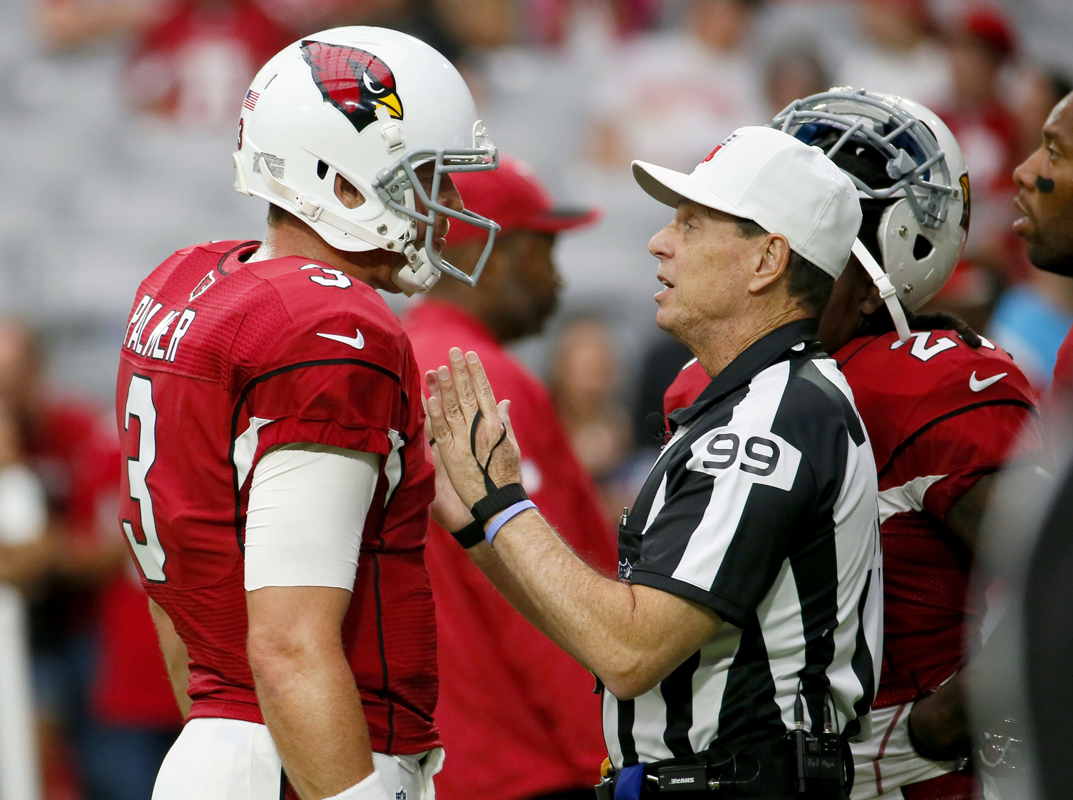 FILE - In this Sept. 27, 2015, file photo, Arizona Cardinals quarterback Carson Palmer (3) talks with referee Tony Corrente (99) prior to an NFL football game against the San Francisco 49ers, in Glendale, Ariz. Three games into the NFL season, yellow flag