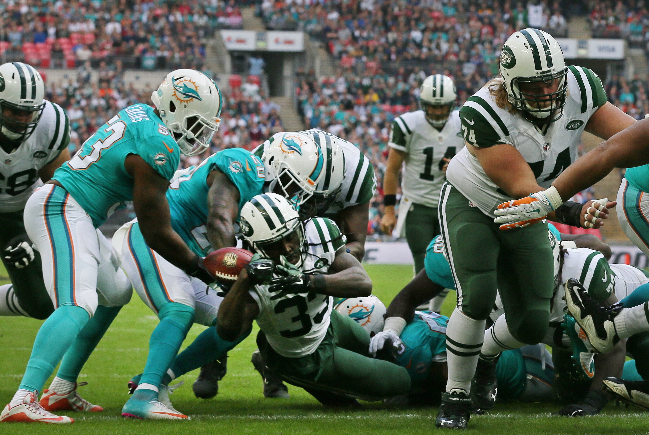 New York Jets' Chris Ivory, center, scores a touchdown during the NFL football game between the New York Jets and the Miami Dolphins and at Wembley stadium in London, Sunday, Oct. 4, 2015. (AP Photo/Tim Ireland)