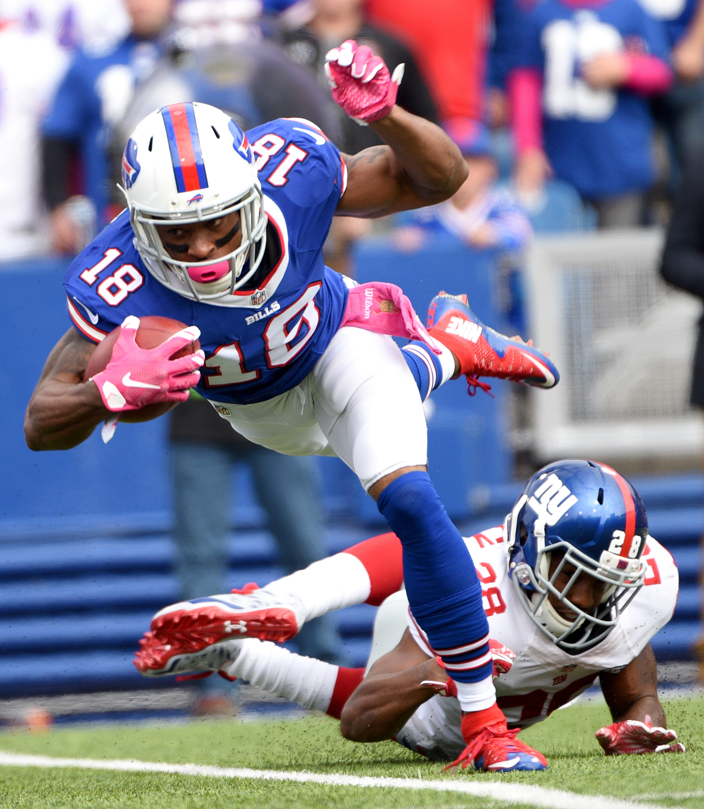 Buffalo Bills wide receiver Percy Harvin (18) is tripped by New York Giants cornerback Jayron Hosley (28) while returning the opening kickoff during the first half of an NFL football game, Sunday, Oct. 4, 2015, in Orchard Park, N.Y. (AP Photo/Gary Wiepert