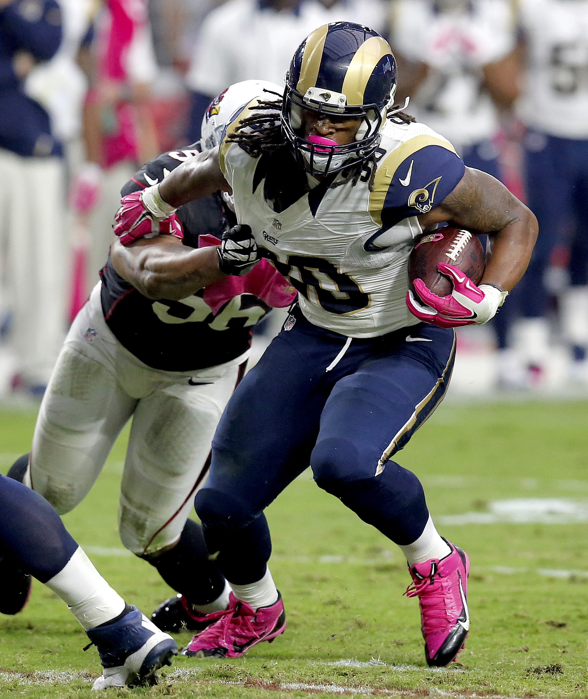 St. Louis Rams running back Todd Gurley (30) eludes the reach of Arizona Cardinals outside linebacker LaMarr Woodley (56) during the second half of an NFL football game, Sunday, Oct. 4, 2015, in Glendale, Ariz. (AP Photo/Rick Scuteri)