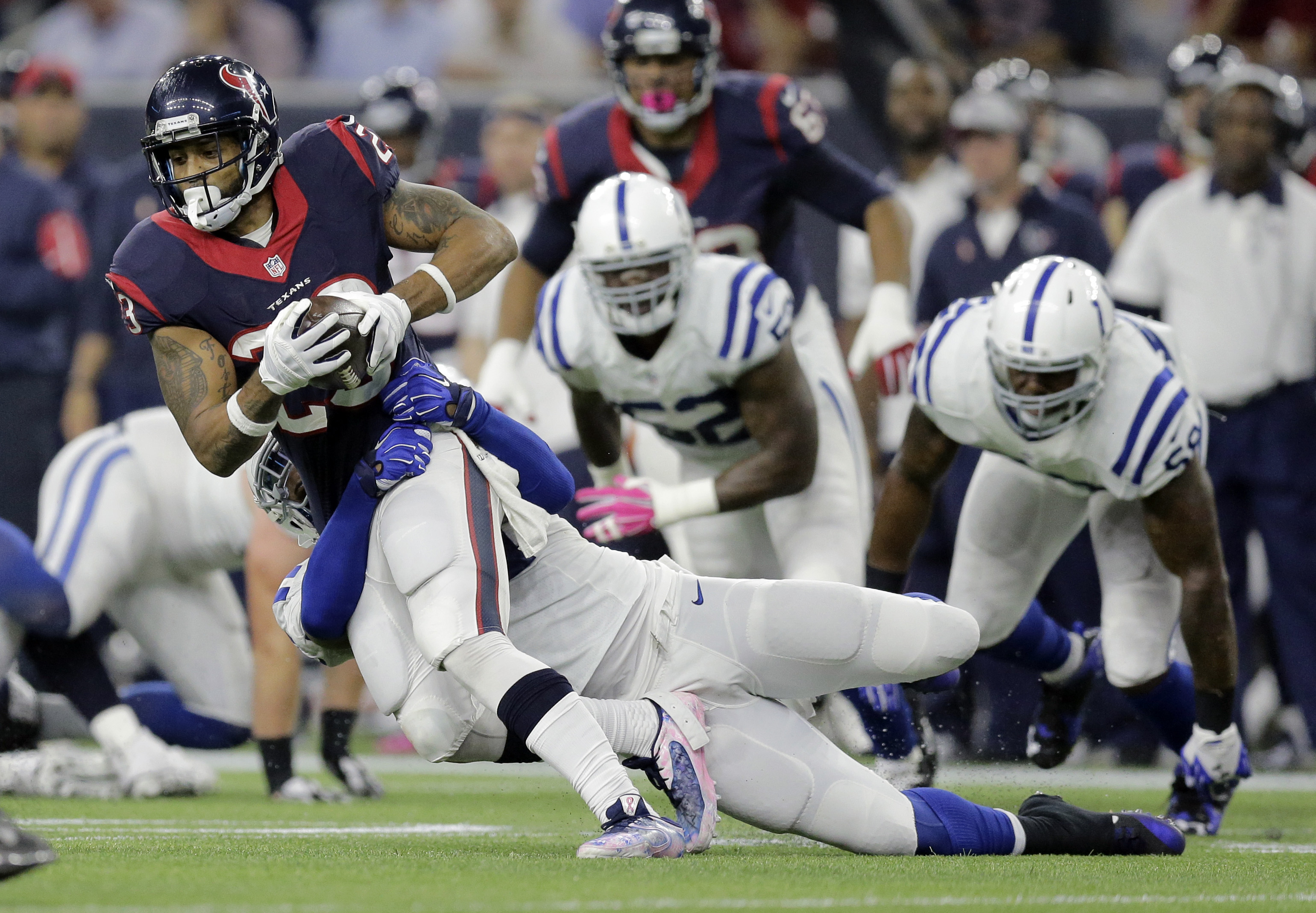 Houston Texans' Arian Foster (23) is stopped by Indianapolis Colts' Jonathan Newsome (91) during the first half of an NFL football game Thursday, Oct. 8, 2015, in Houston. (AP Photo/Patric Schneider)