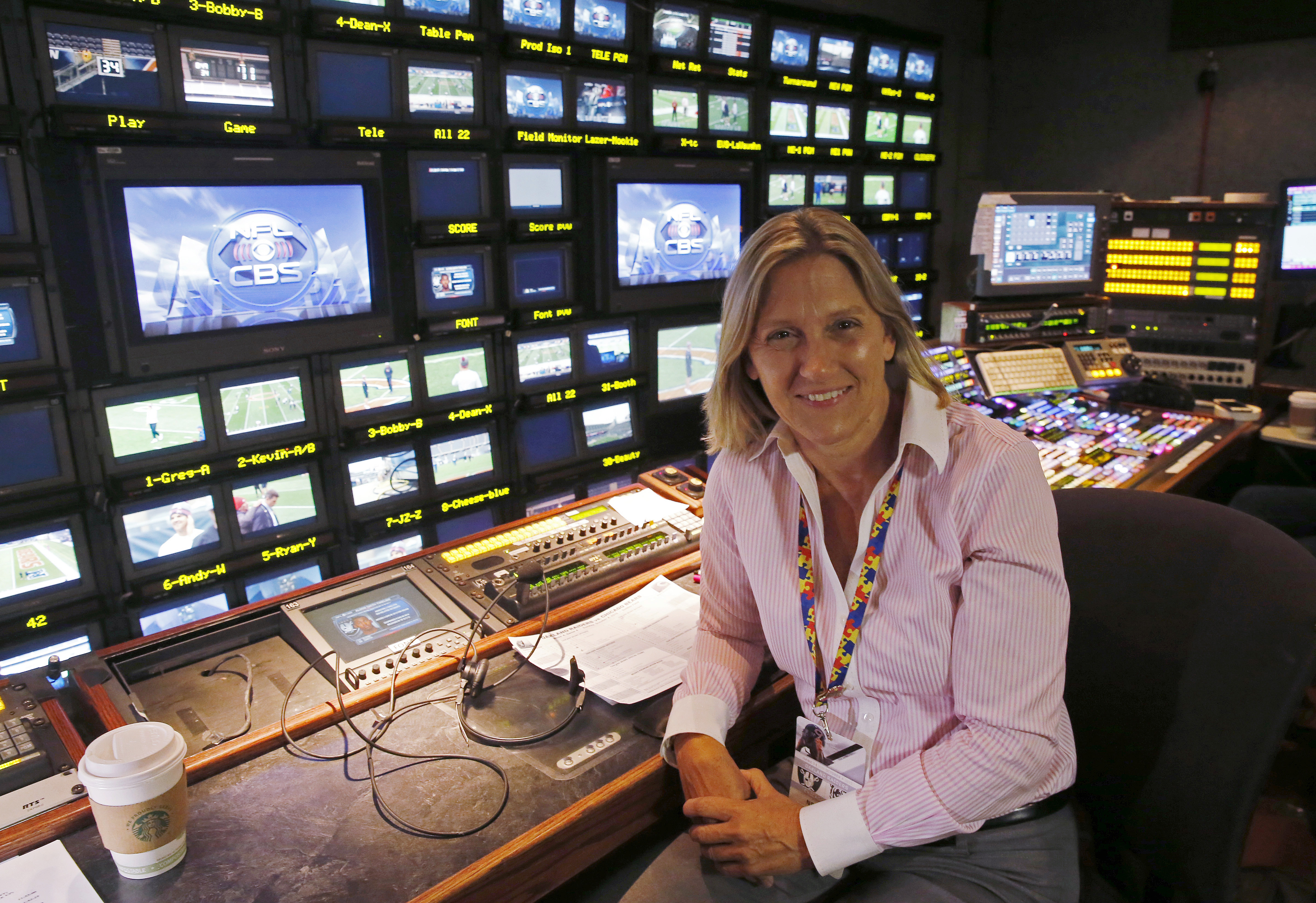 In this Sunday, Oct. 4, 2015, photo, CBS's Suzanne Smith poses for photos as she directs a pre-game show before an NFL football game between the Chicago Bears and the Oakland Raiders in Chicago. As the only woman currently directing NFL games, Smith influ
