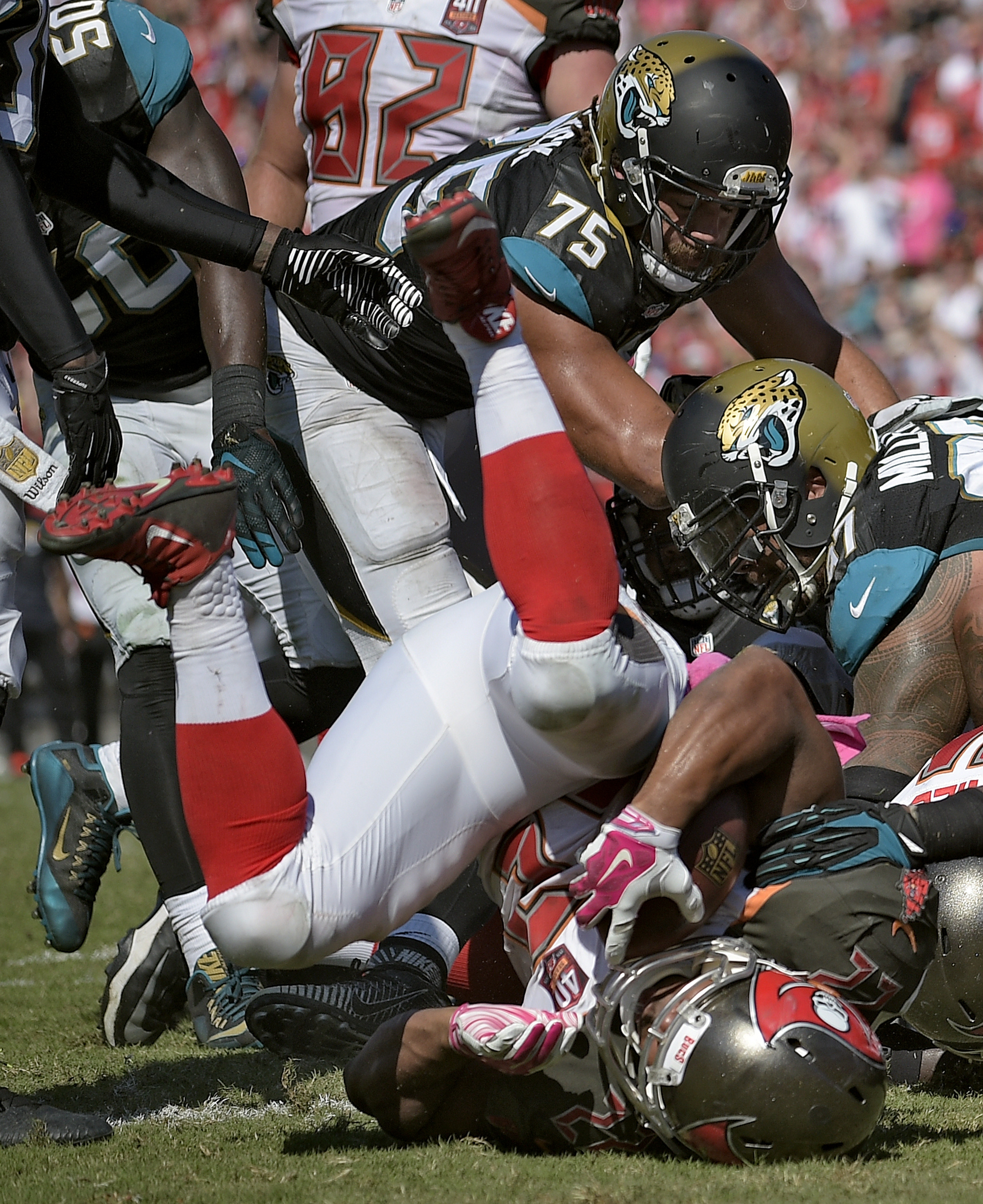 Tampa Bay Buccaneers running back Doug Martin (22) flips over Jacksonville Jaguars defensive end Jared Odrick (75) after scoring on a 1-yard touchdown run during the fourth quarter of an NFL football game Sunday, Oct. 11, 2015, in Tampa, Fla. (AP Photo/Ph