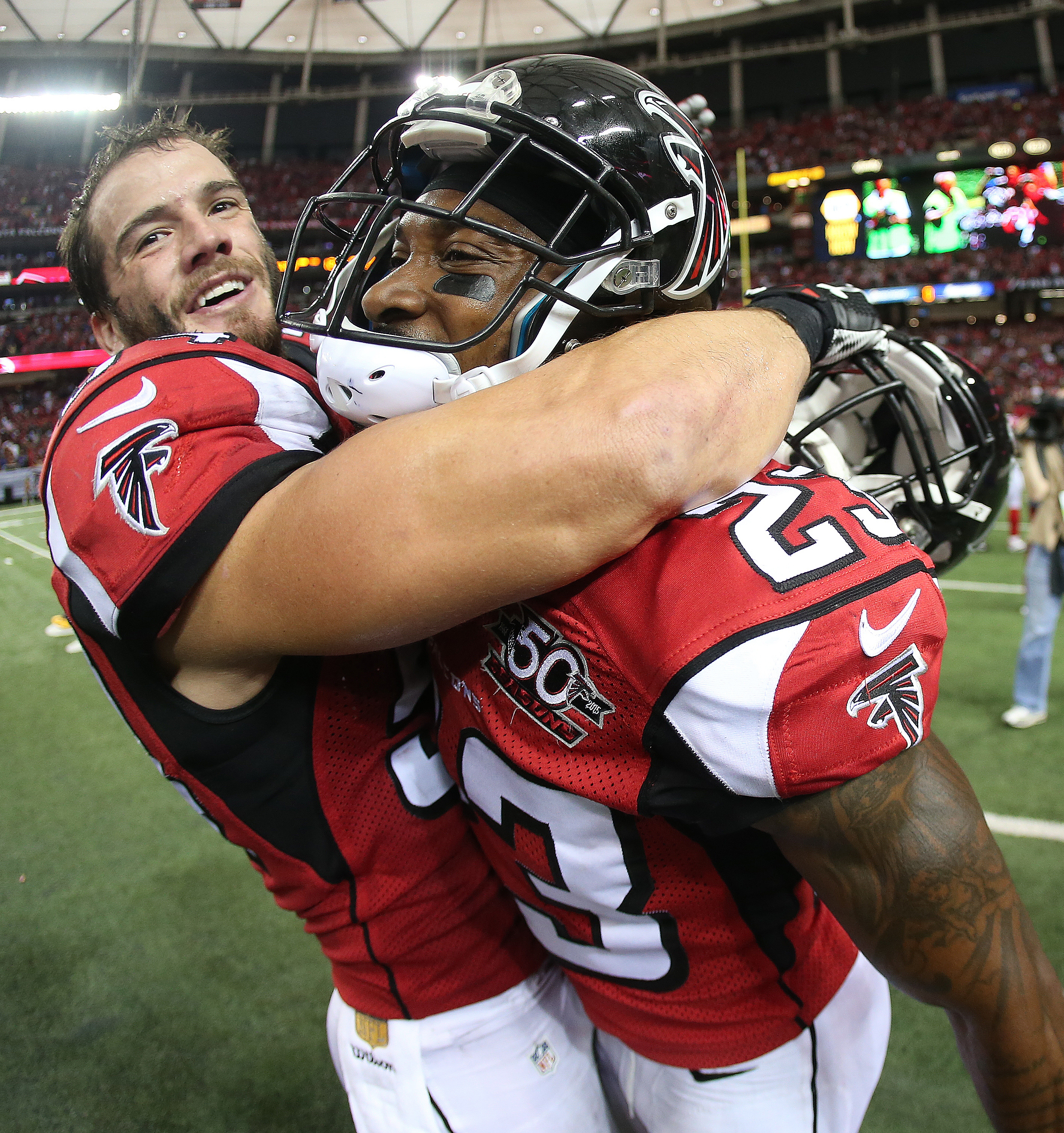 Atlanta Falcons outside linebacker Nate Stupar, left, embraces Atlanta Falcons cornerback Robert Alford (23) after Alford picked off Washington Redskins quarterback Kirk Cousins (8) and scored a touchdown during the overtime of an NFL football game, Sunda