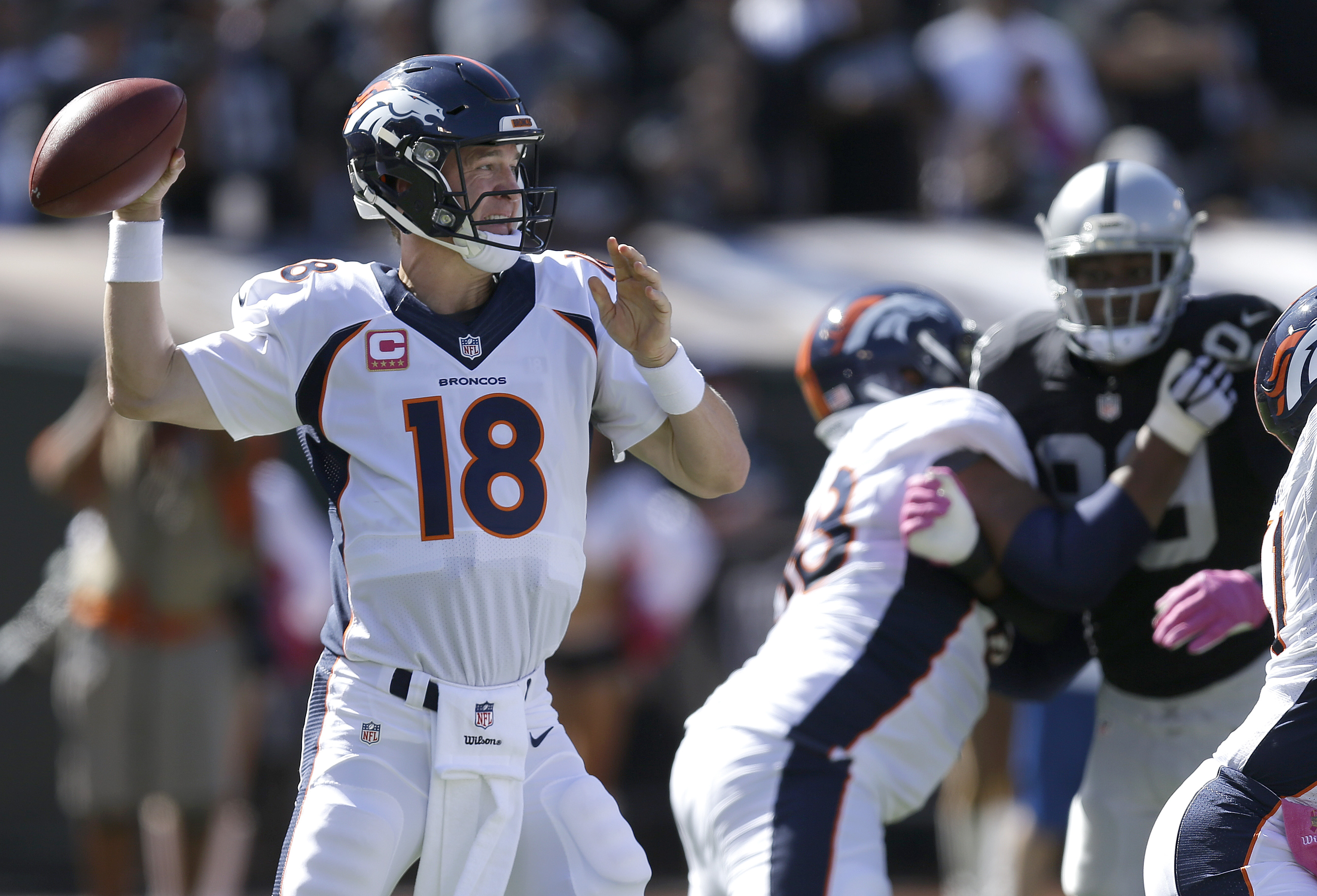 Denver Broncos quarterback Peyton Manning (18) passes against the Oakland Raiders during the first half of an NFL football game in Oakland, Calif., Sunday, Oct. 11, 2015. (AP Photo/Ben Margot)