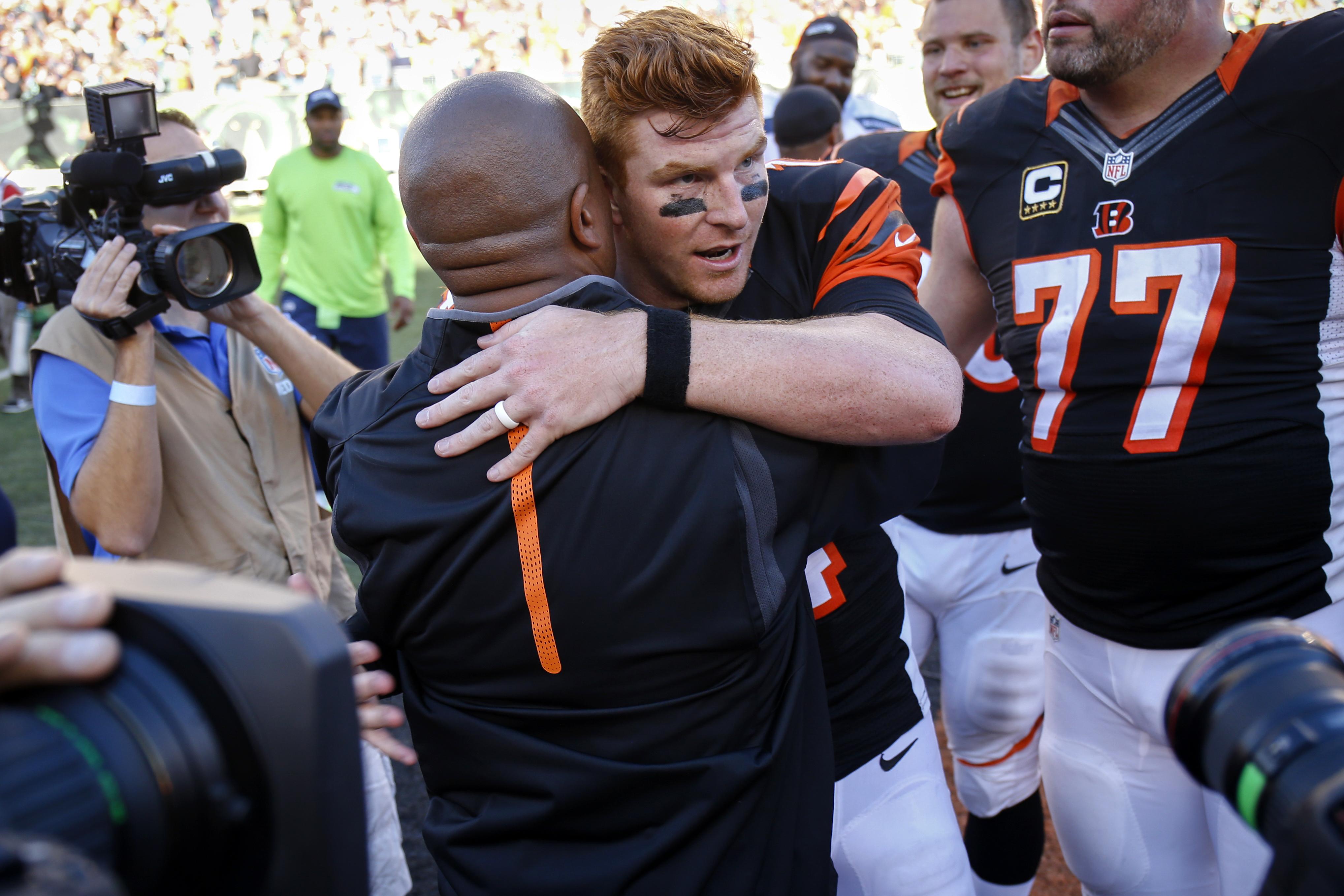 Cincinnati Bengals quarterback Andy Dalton, center right, hugs offensive coordinator Hue Jackson after an NFL football game against the Seattle Seahawks, Sunday, Oct. 11, 2015, in Cincinnati. The Bengals won 27-24. (AP Photo/Gary Landers)
